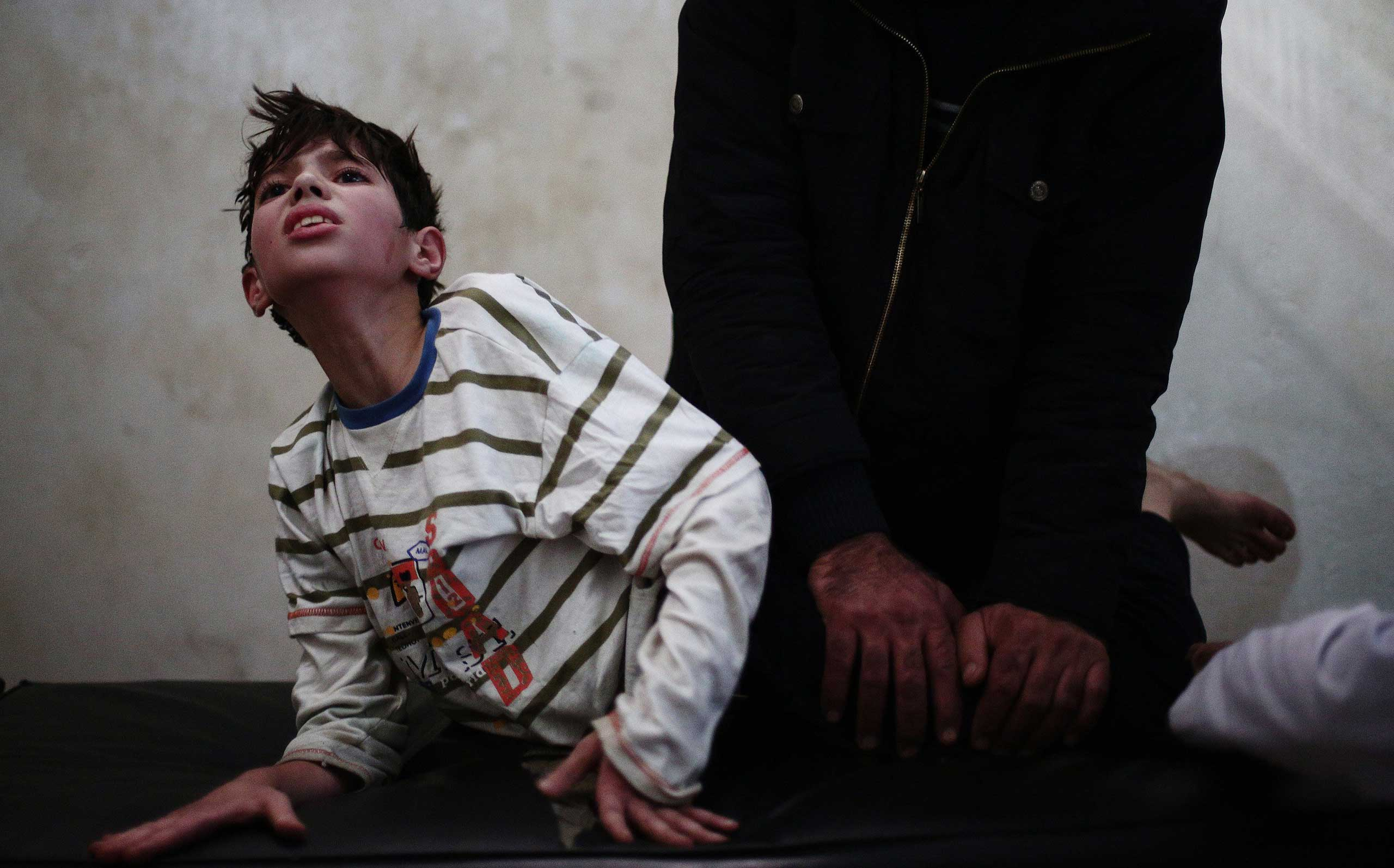 Nov. 6, 2014. A doctor stretches the legs of Syrian youth Mustafa at a physical therapy center  in Eastern al-Ghouta, a rebel-held region outside the capital Damascus. Mustafa, 13, had his legs' tendons cut after he was injured in an airstrike four months before.