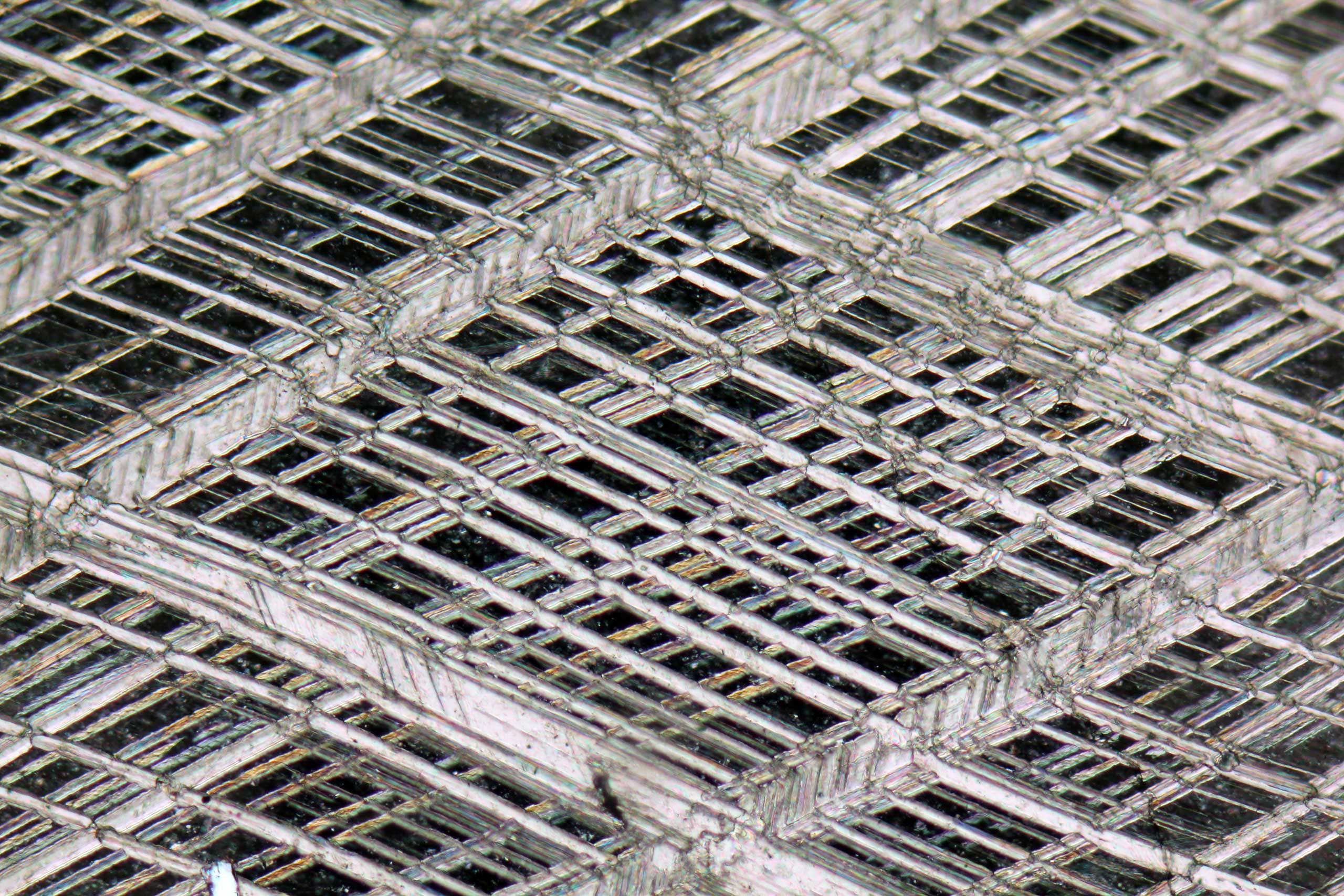 A rhombohedral cleavage in calcite crystal at 10x magnification.
