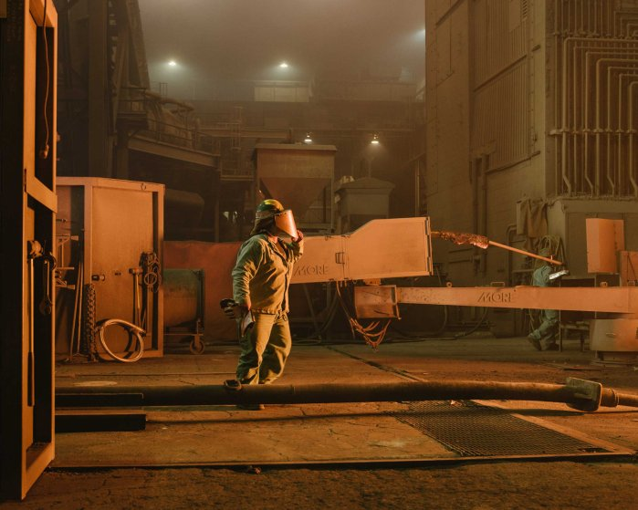 A worker approaches the electric-arc furnace, which uses three giant electrodes to melt scrap into molten steel at Nucor mill in Crawfordsville, Ind. on Aug. 25, 2014.