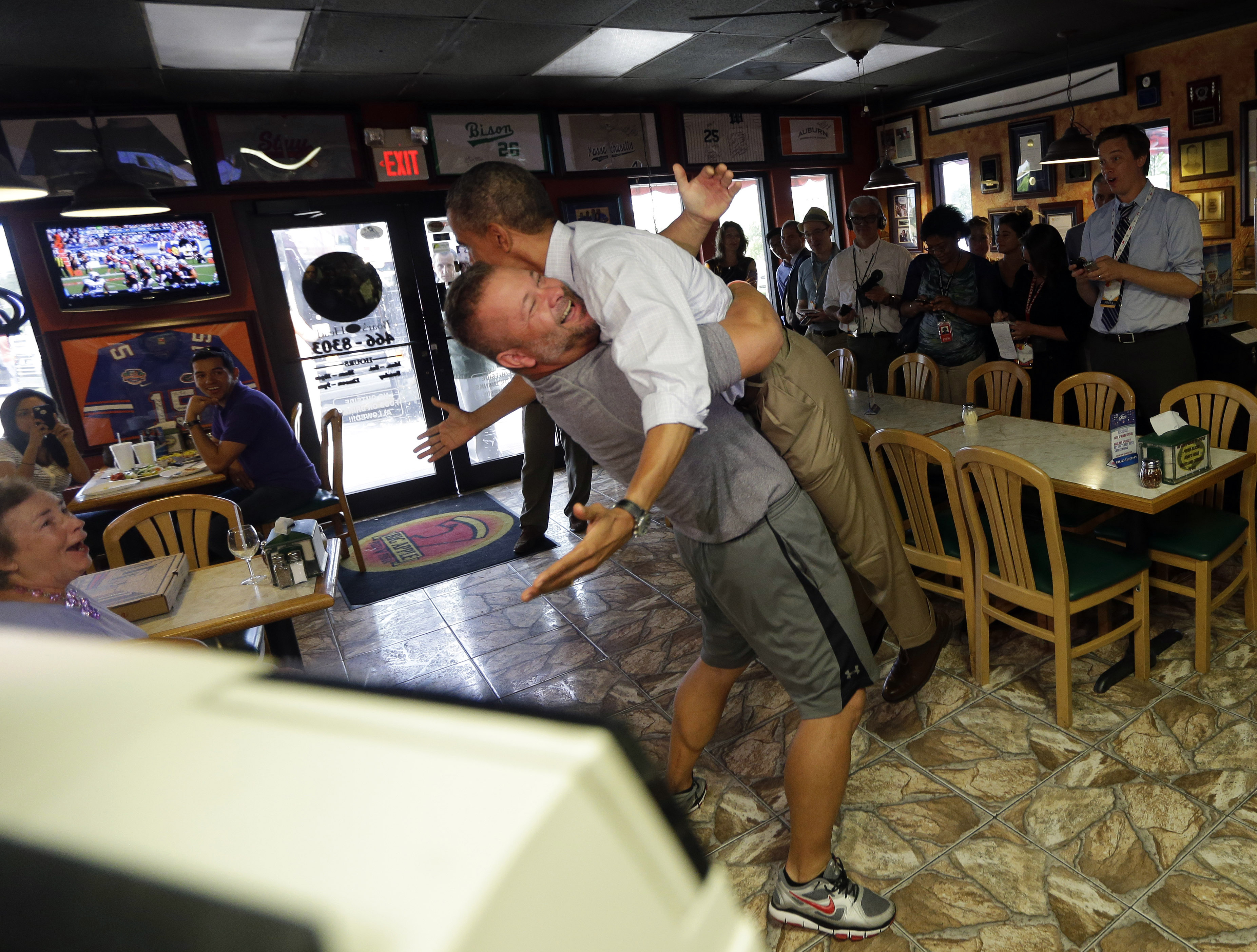 "Obama was literally swept off his feet by pizzeria owner Scott Van Duzer.  The now-famous bear hug was a ""celebrities are just like us"" moment, when Obama showed he could still joke around in a regular ol' pizza joint. Sept. 9, 2012."