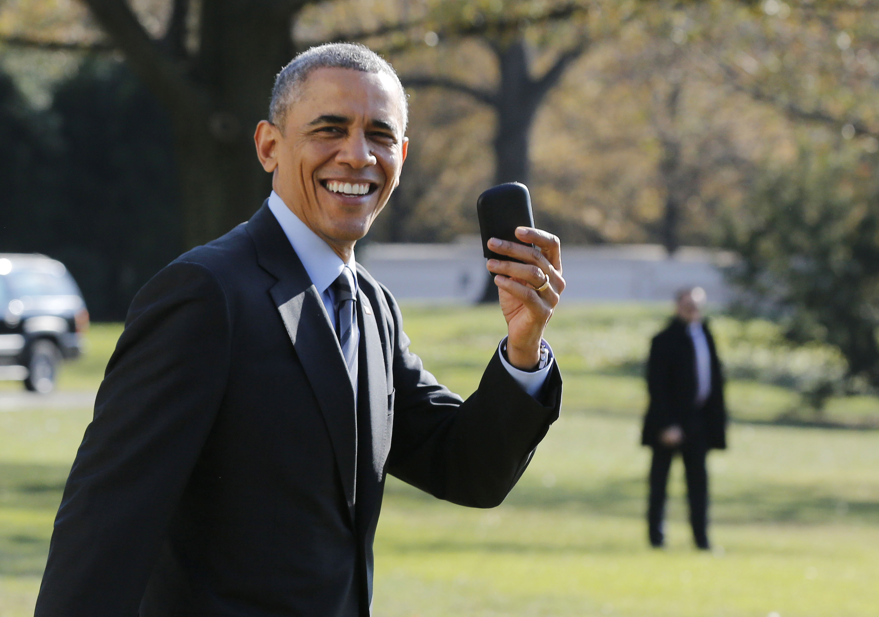 U.S. President Barack Obama holds up his BlackBerry device after he returned inside the White House to retrieve it, after boarding Marine One on the South Lawn of the White House in Washington on Nov. 21, 2014.