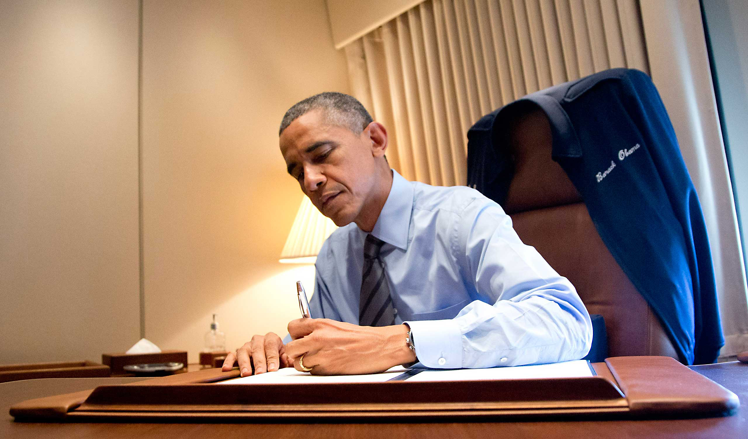 President Barack Obama signs two presidential memoranda associated with his actions on immigration in his office, on Air Force One as he arrives at McCarran International Airport in Las Vegas, Nov. 21, 2014.