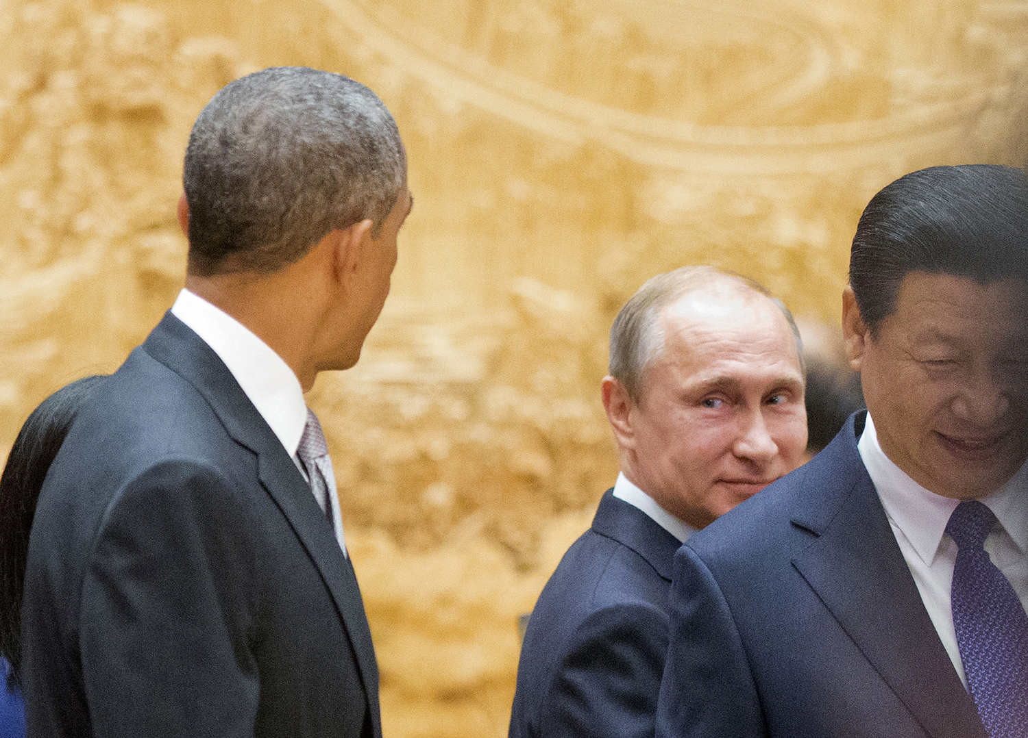 Russian President Vladimir Putin, center, looks back at U.S. President Barack Obama, left, as they arrive with Chinese President Xi Jinping, right, at an Asia-Pacific Economic Cooperation summit plenary session in Beijing on Nov. 11, 2014