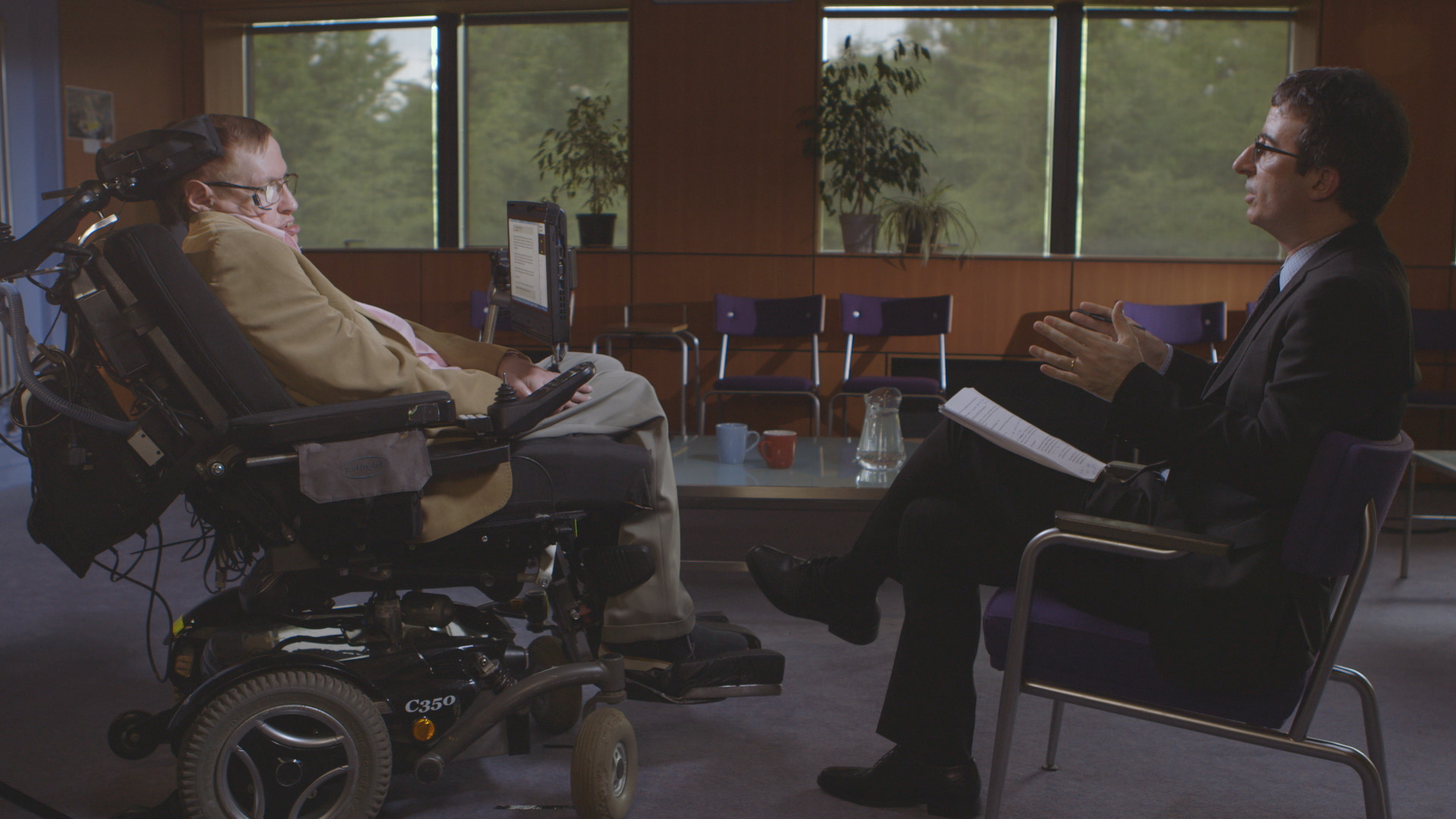 Oliver, at right, interviews Stephen Hawking