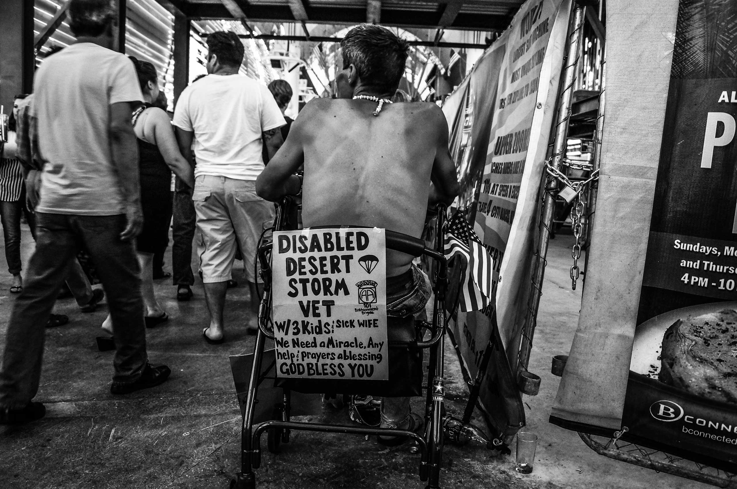 July 4, 2013. The Strip, Las Vegas.                                                               A disabled war veteran looks toward a crowd, hoping that someone passing by will give him spare change to help support his family.
