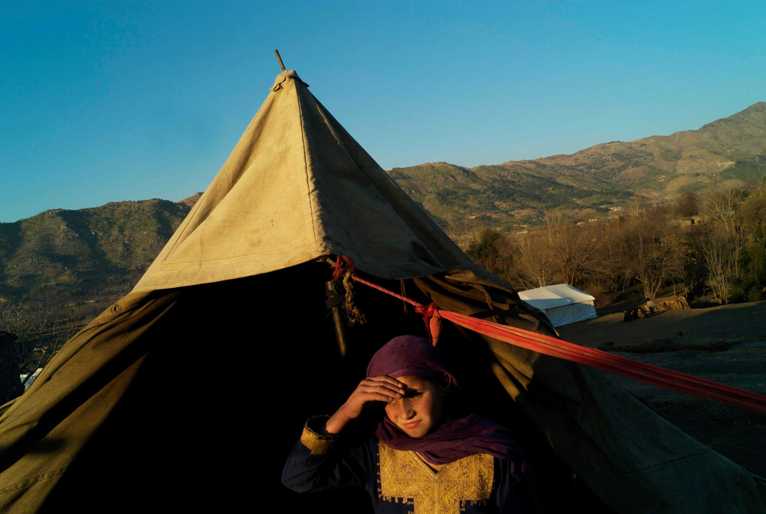 SADBARKALAI, PAKISTAN- FEBRUARY 2011                                Shielding her eyes from the sun as it sets behind the mountains of Afghanistan, 11 year old Shaheeda stands outside her family's tent in an IDP camp at Sadbarkalai.