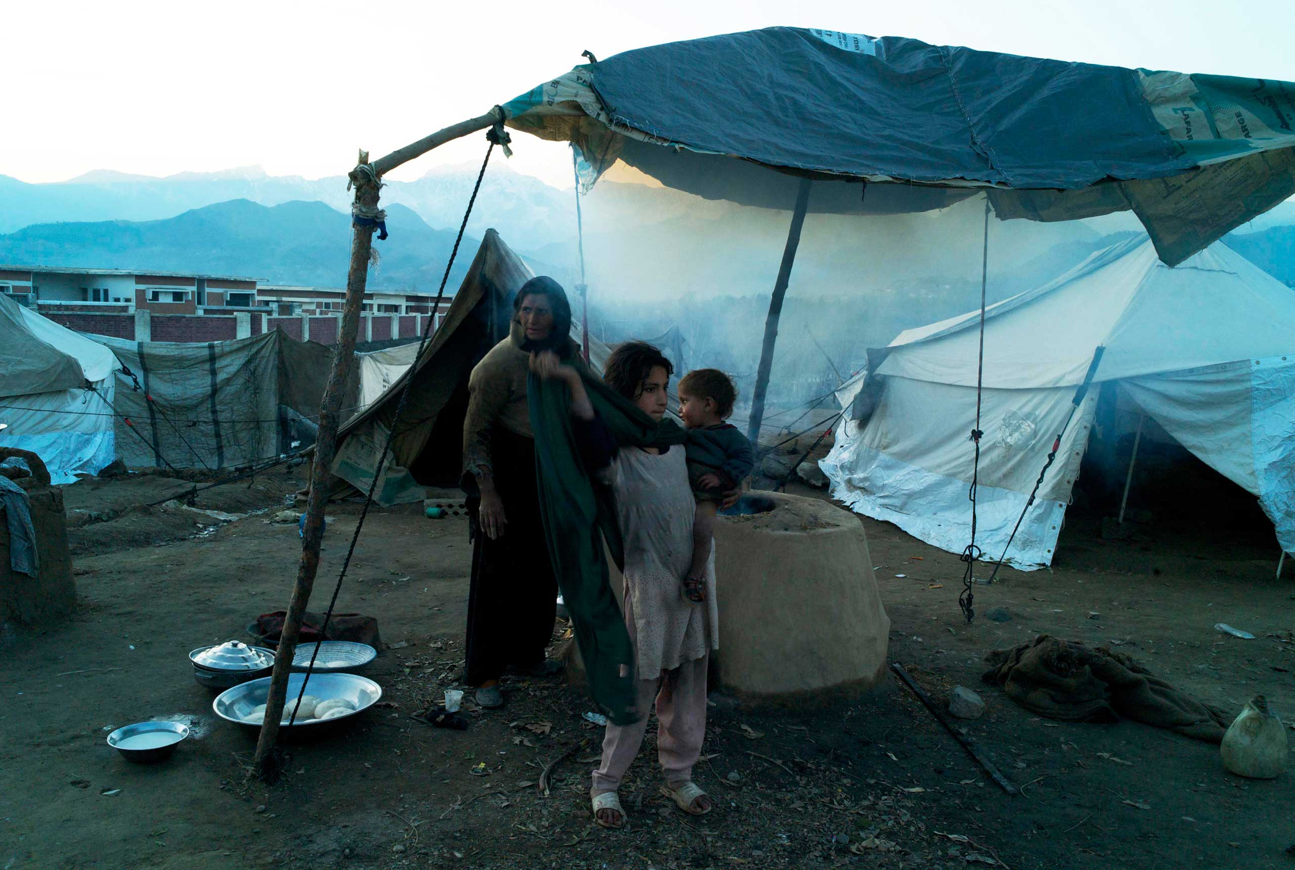 SADBARKALAI, PAKISTAN- FEBRUARY 2011                                Shrouded in smoke from a mud built tandoor, 12 year old Tayeeba holds her 18 month old baby brother Abbas as she helps her mother to prepare rotis for an evening meal in the cold winter's air outside their tent in Sadbarkalai.