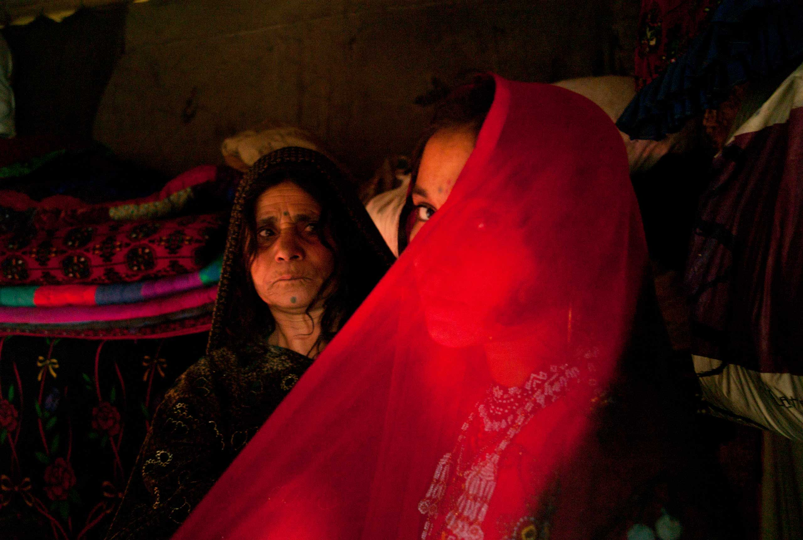 LAHORE, PAKISTAN- NOVEMBER 2009                               A few days ahead of her wedding, 14 year old Afghan refugee Zeenat Gul is helped by her mother as she tries on her hand made red beaded wedding dress at their one room home in the slums of Sagiam Pull.                               One of ten siblings, Zeenat was born at the refugee camp of Kohart in Pakistan's North West Frontier Province after her family fled fighting in Kunduz.                               Zeenat Gul has yet to meet her fiance but has been busy making her in-laws to be gifts of beaded combs, mirrors and jewelry. Now liberated from her work in the dump, her mother Barangul has been advising her teenage daughter about marriage. The sensitive topic of sex will not be raised until the wedding night,  When a girl marries, then she will become a woman .