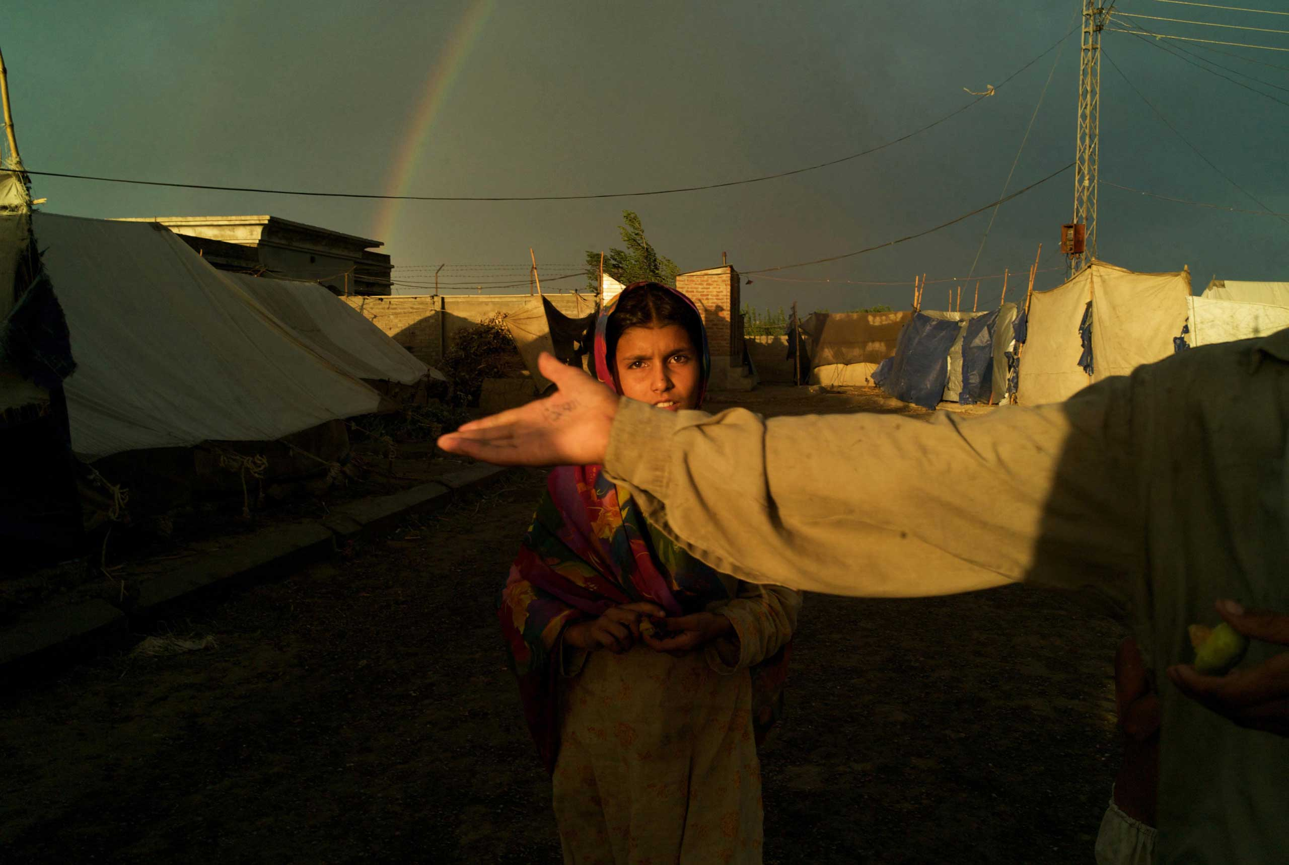 CHARSADDA, PAKISTAN- JUNE 2009                               Under the arc of a rainbow, a girl makes her way through a tented camp in Charsadda located in the grounds of a technical college. Home to nearly 25,000 refugees from Bajaur, the  camp was one of the first to be established as conflict in Pakistan's tribal areas began nearly a year ago.
