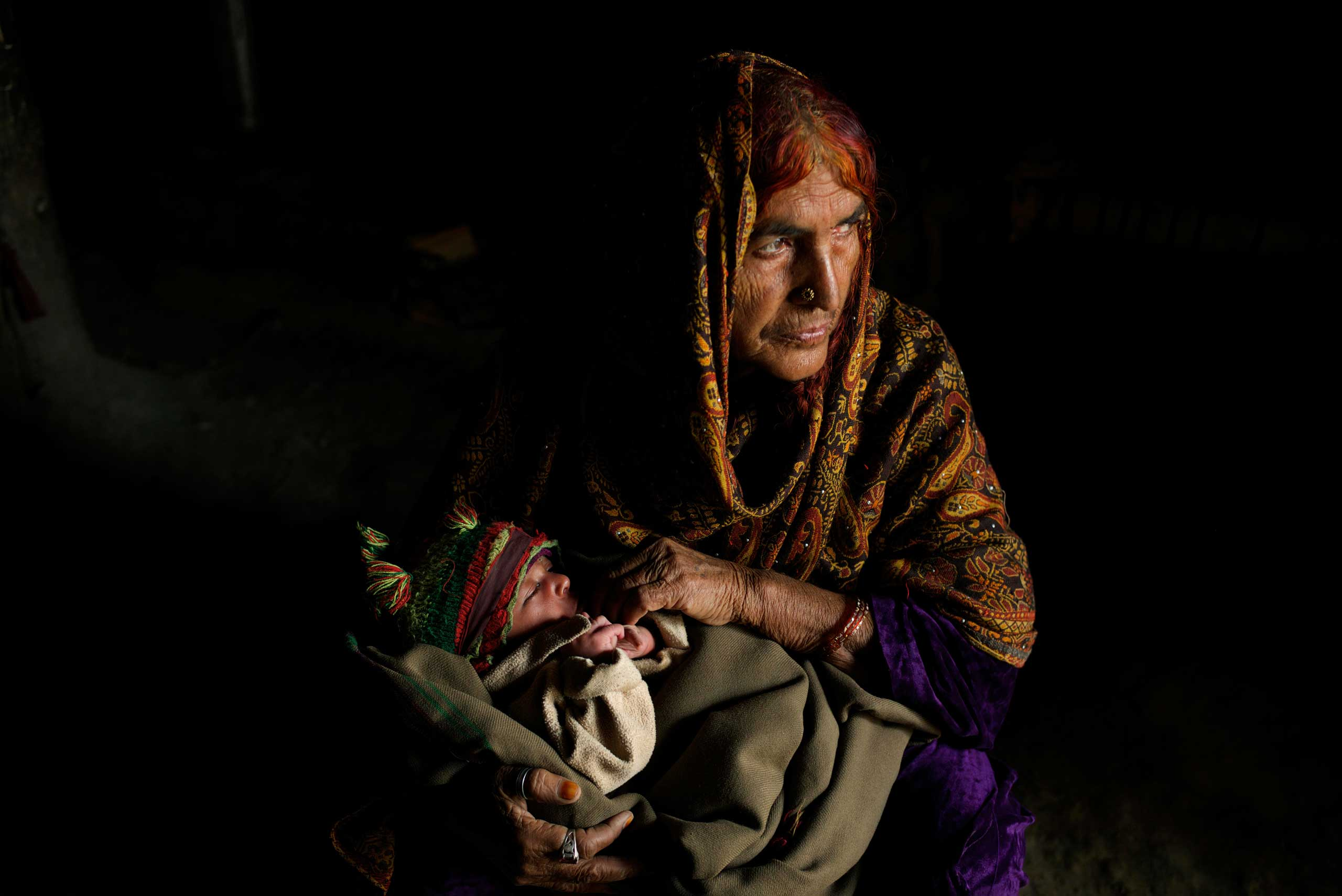 ISLAMABAD, PAKISTAN; FEBRUARY 2104                                Holding her 25 day old grandson Ziaullah, elderly Bacha Hilal squats down in the mud hut that has become home since escaping conflict in Bajaur.