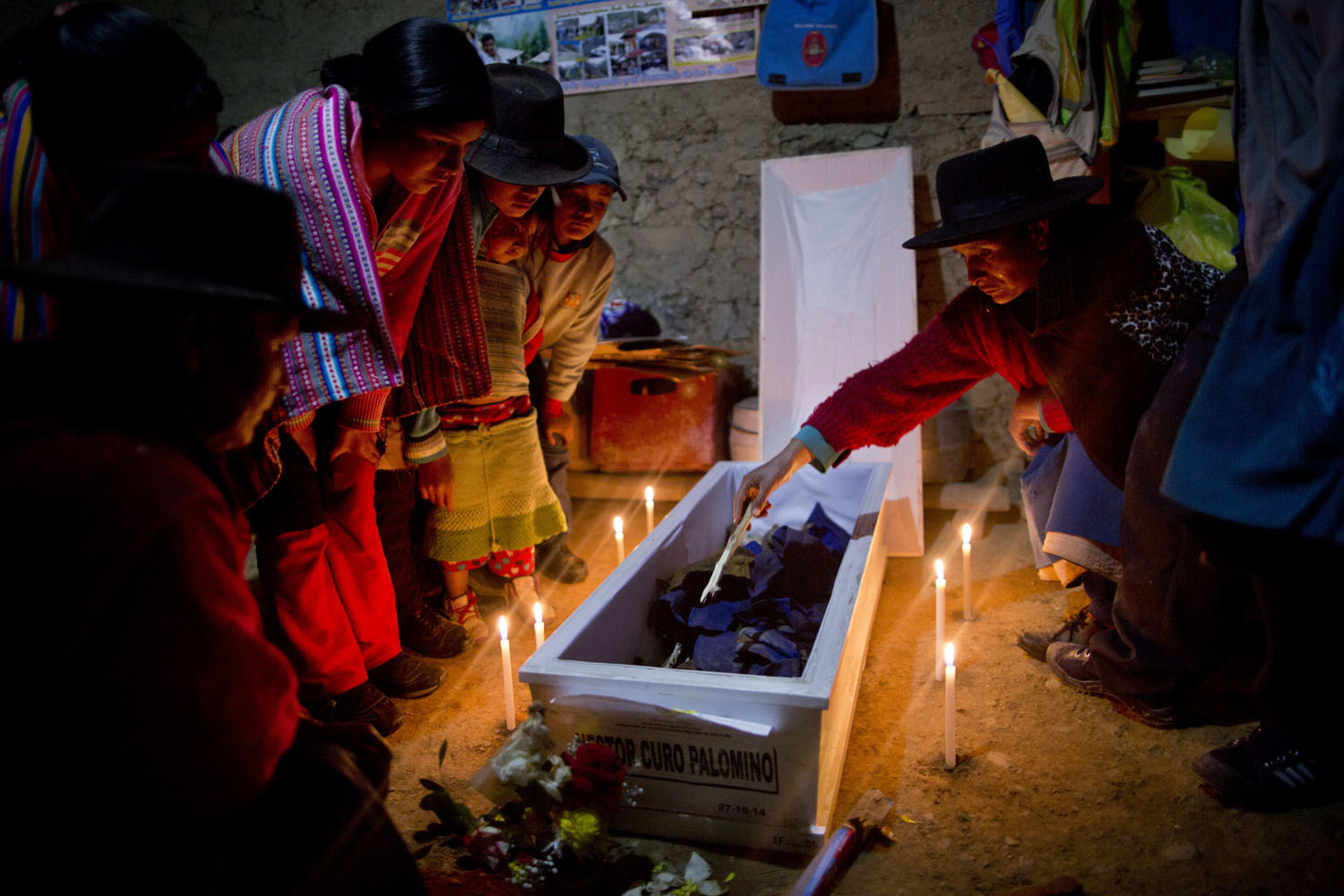 From the series: Peru's Dirty War VictimsTears run down Udilia Ciguria Curo's face as she slowly inspect the remains of her brother Hector Curo Palomino during a one day candle lit wake inside the their home, as is local custom, in Huallhua, in Peru's Ayahuanco region, Oct. 28, 2014. Curo was in his 20s when he was killed defending the town with two other members of the village's citizen self-defense force so villagers could escape from Shining Path militants on June 14, 1990. His remains were only recently exhumed and handed over to relatives, allowing them to bury him properly 24 years later.