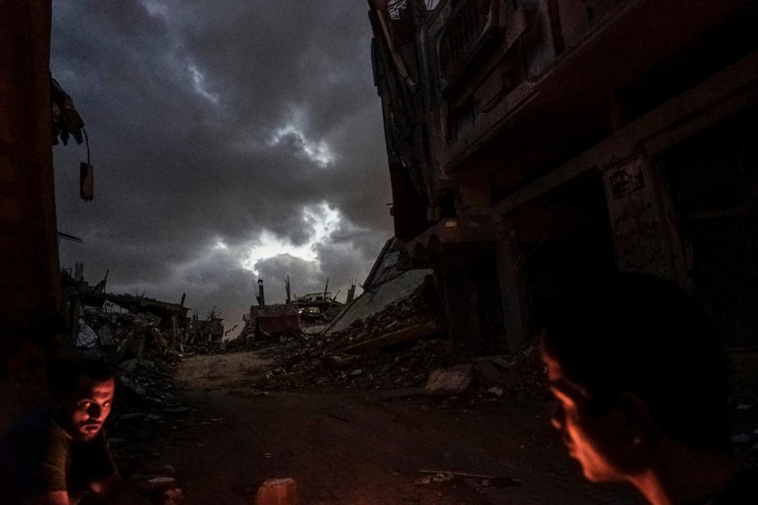 2014.  Gaza.  Palestine. Two men warm themselves by a fire in the destroyed Shujai'iya neighborhood.  Operation Protective Edge lasted from 8 July 2014 – 26 August 2014, killing 2,189 Palestinians of which 1,486 are believed to be civilians. 66 Israeli soldiers and 6 civilians were killed.  It's estimated that 4,564 rockets were fired at Israel by Palestinian militants.