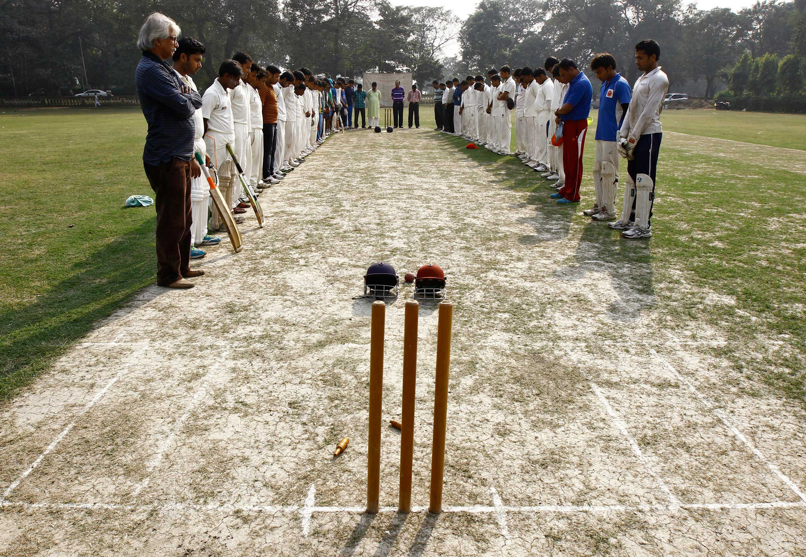 Nov. 27, 2014. Members of two local cricket teams observe a moment of silence for Australian cricketer Phillip Hughes before their match in Kolkata, India. Hughes died in a Sydney hospital, two days after being struck by a cricket ball during a match in Australia.
