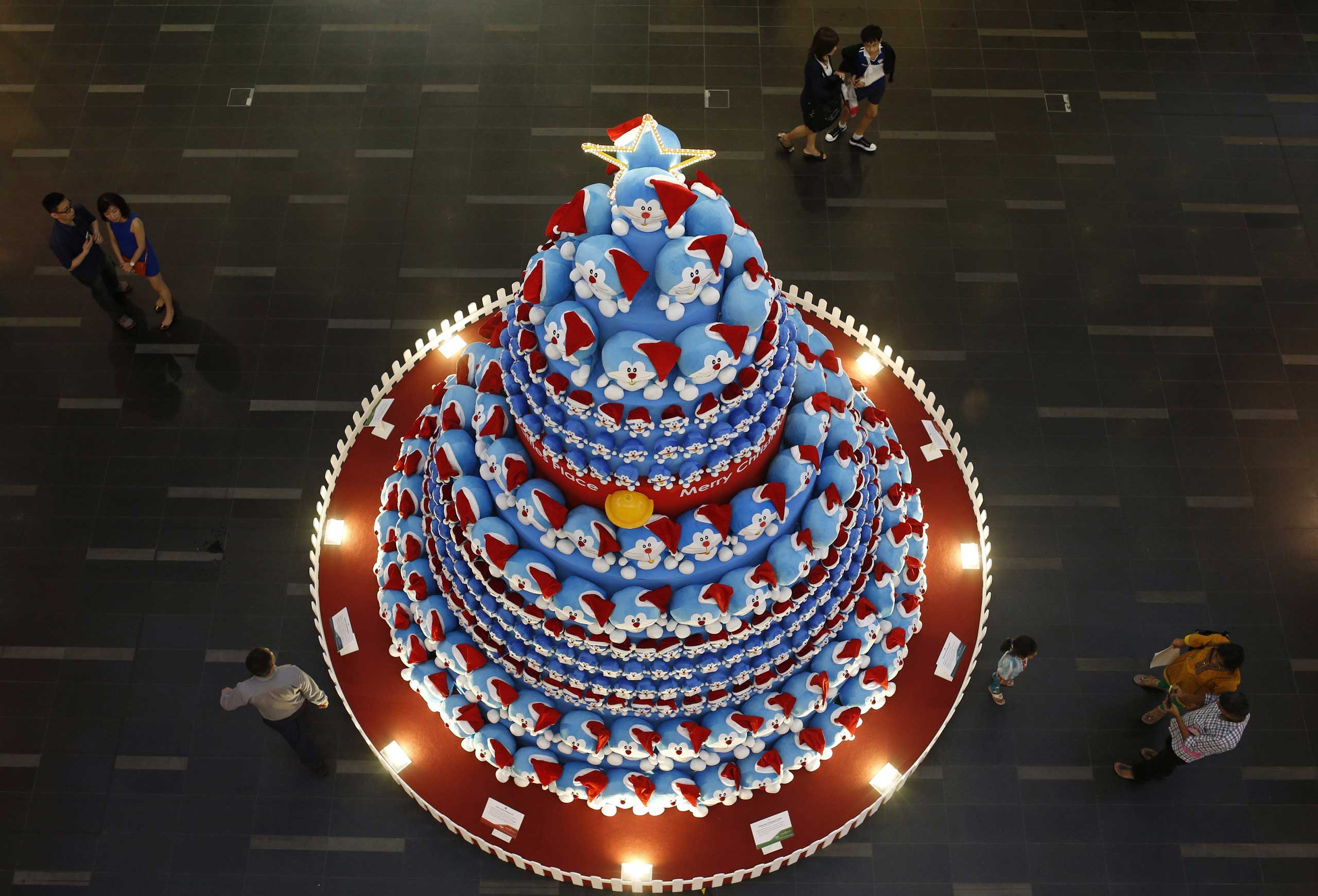 Nov. 24, 2014. People take photos of a Christmas tree made up of Japanese Manga character Doraemon at a shopping mall in the central business district in Singapore.