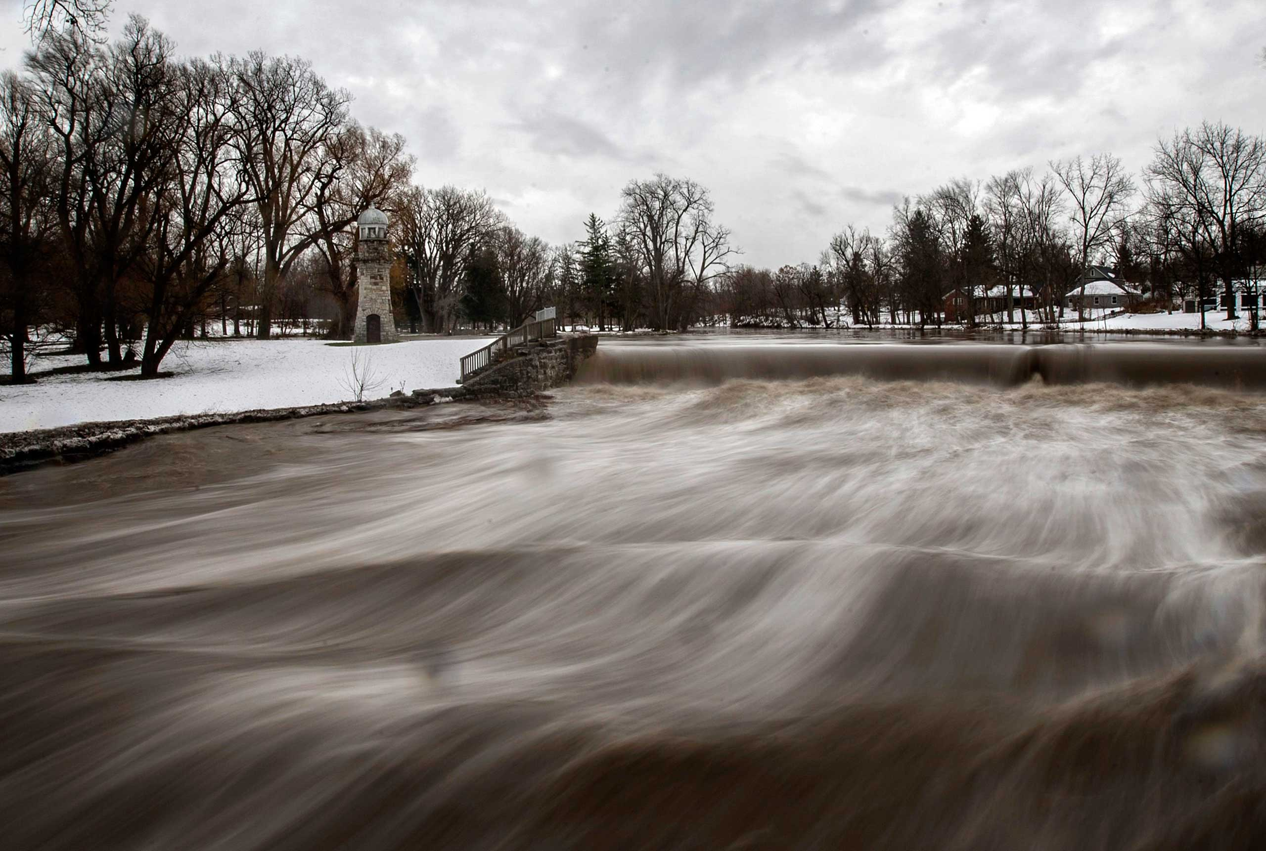 Nov. 24, 2014. Cayuga Creek water rushes past a neighborhood following a massive snow storm in Lancaster, N.Y. The area around Buffalo, N.Y. has potential for flooding as warming temperatures began to melt up to seven feet of snow.