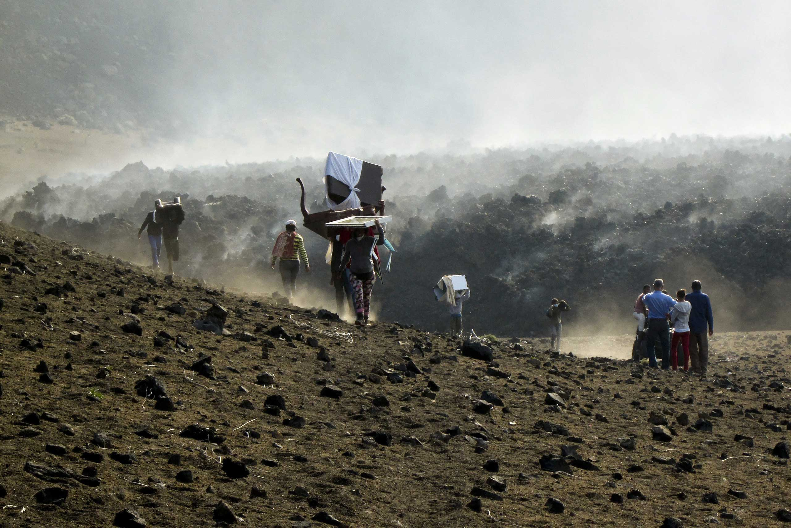 Nov. 25, 2014. Inhabitants of Chã das Caldeiras carry their belongings as they leave the area due to volcano erupting in the island of Fogo, Cape Verde.