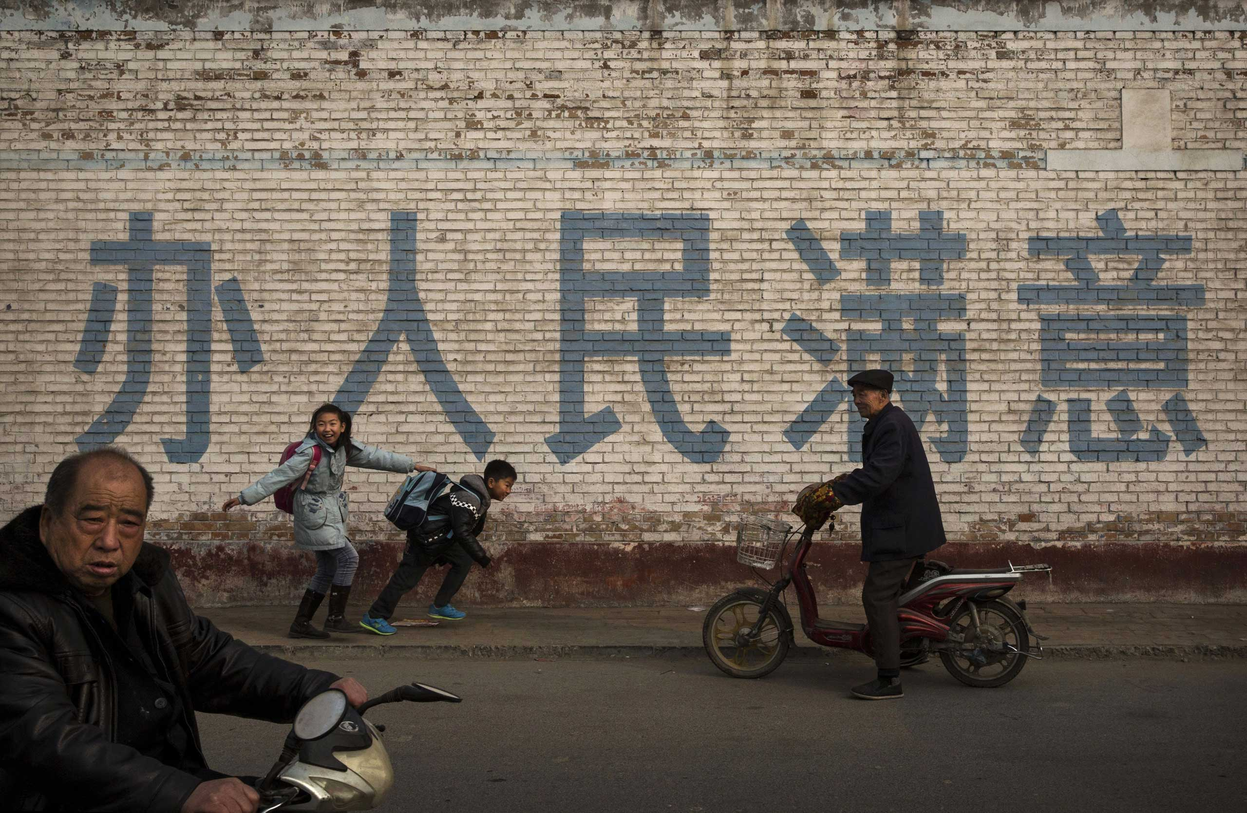 Nov. 21, 2014. Students joke with each other as they walk to school in Heibei province, China. Located near Beijing, the province is considered one of the main industrial centers in China.