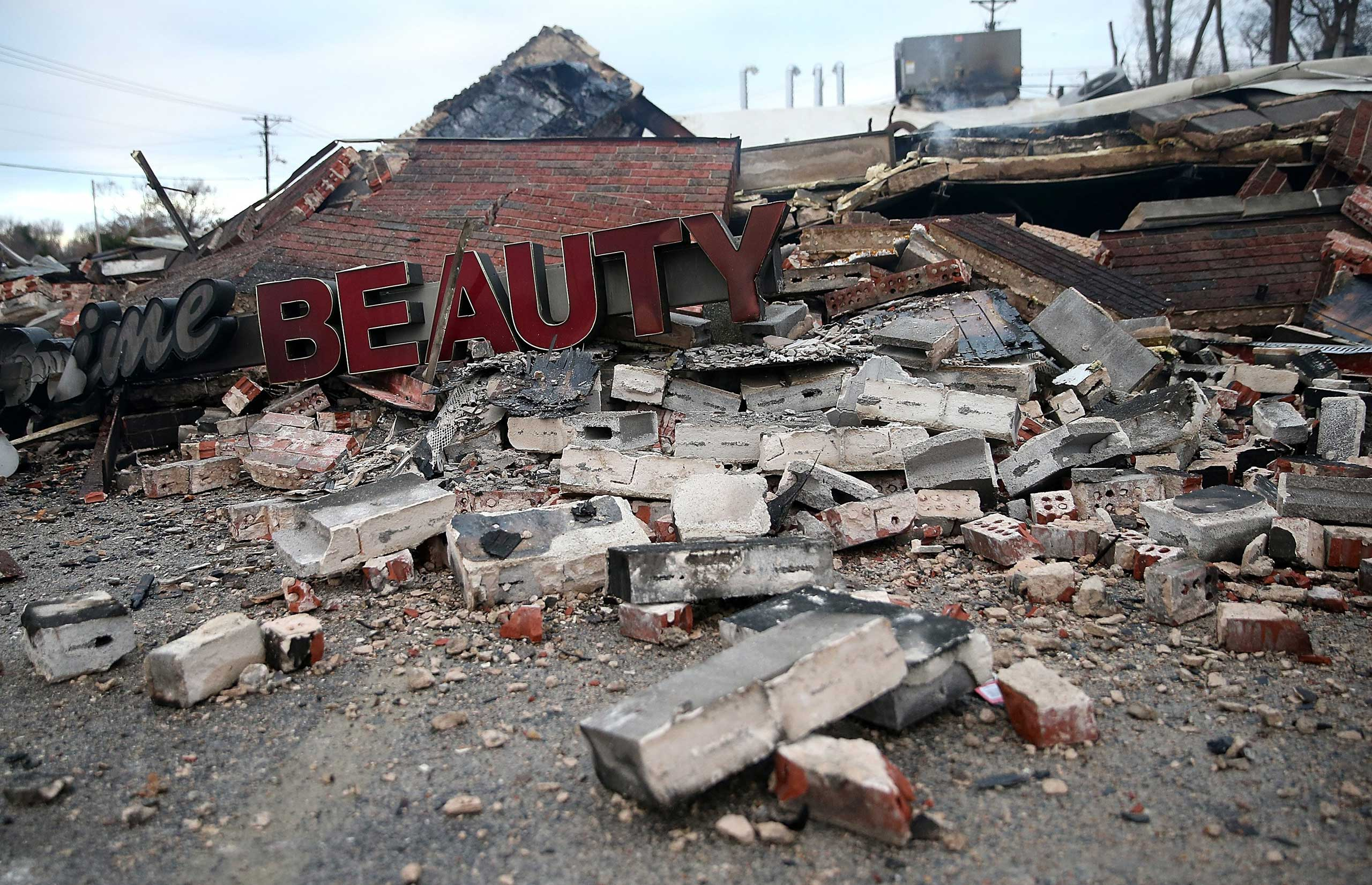 Nov. 25, 2014. A sign sits amid rubble at a building that was damaged during a demonstration in Dellwood, Mo. following the Ferguson grand jury decision.