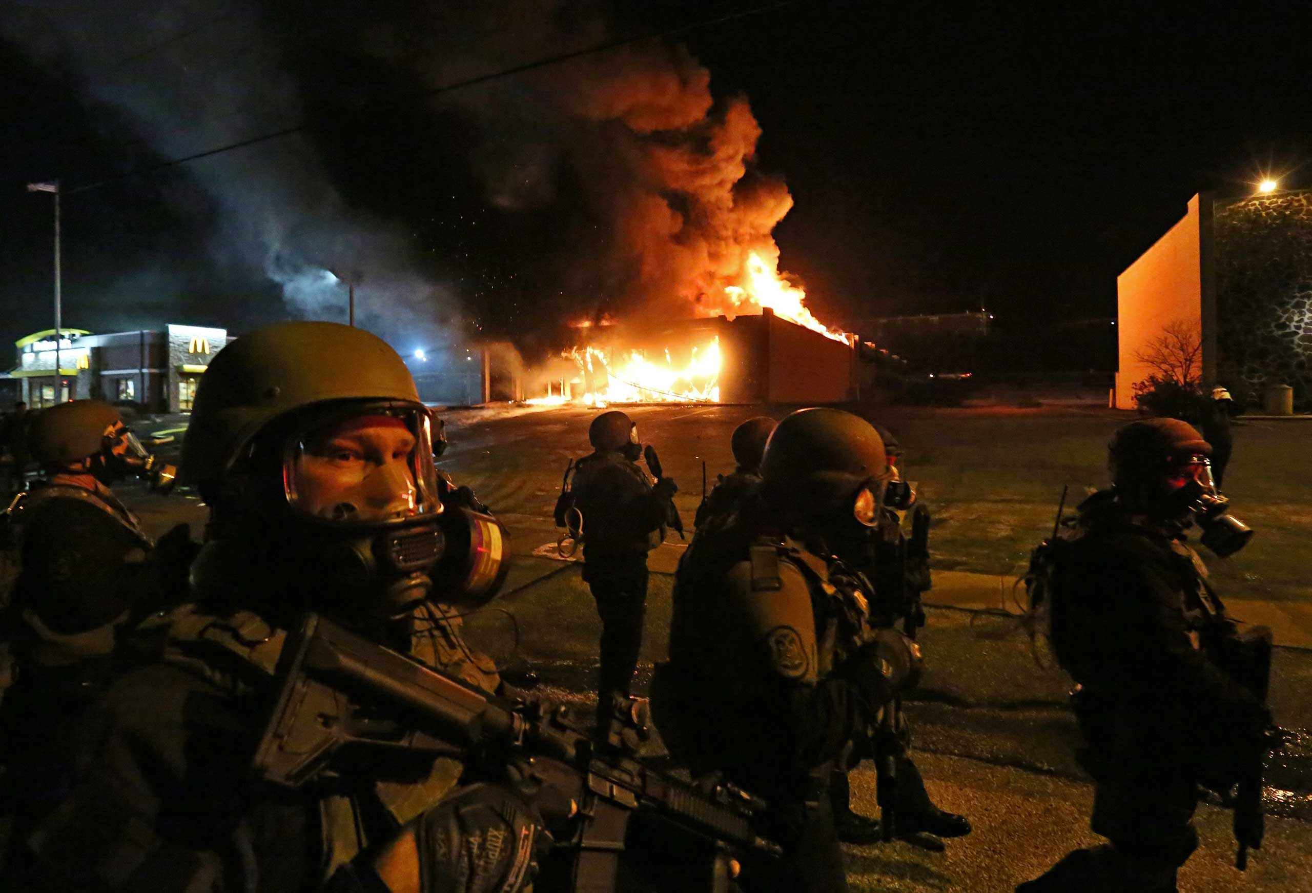 Nov. 24, 2014. St. Louis County Police tactical team arrive on W. Florissant Avenue in Ferguson, Mo., to disperse a crowd as a store burns. A grand jury decided not to indict Ferguson police officer Darren Wilson in the fatal shooting of black teenager Michael Brown.