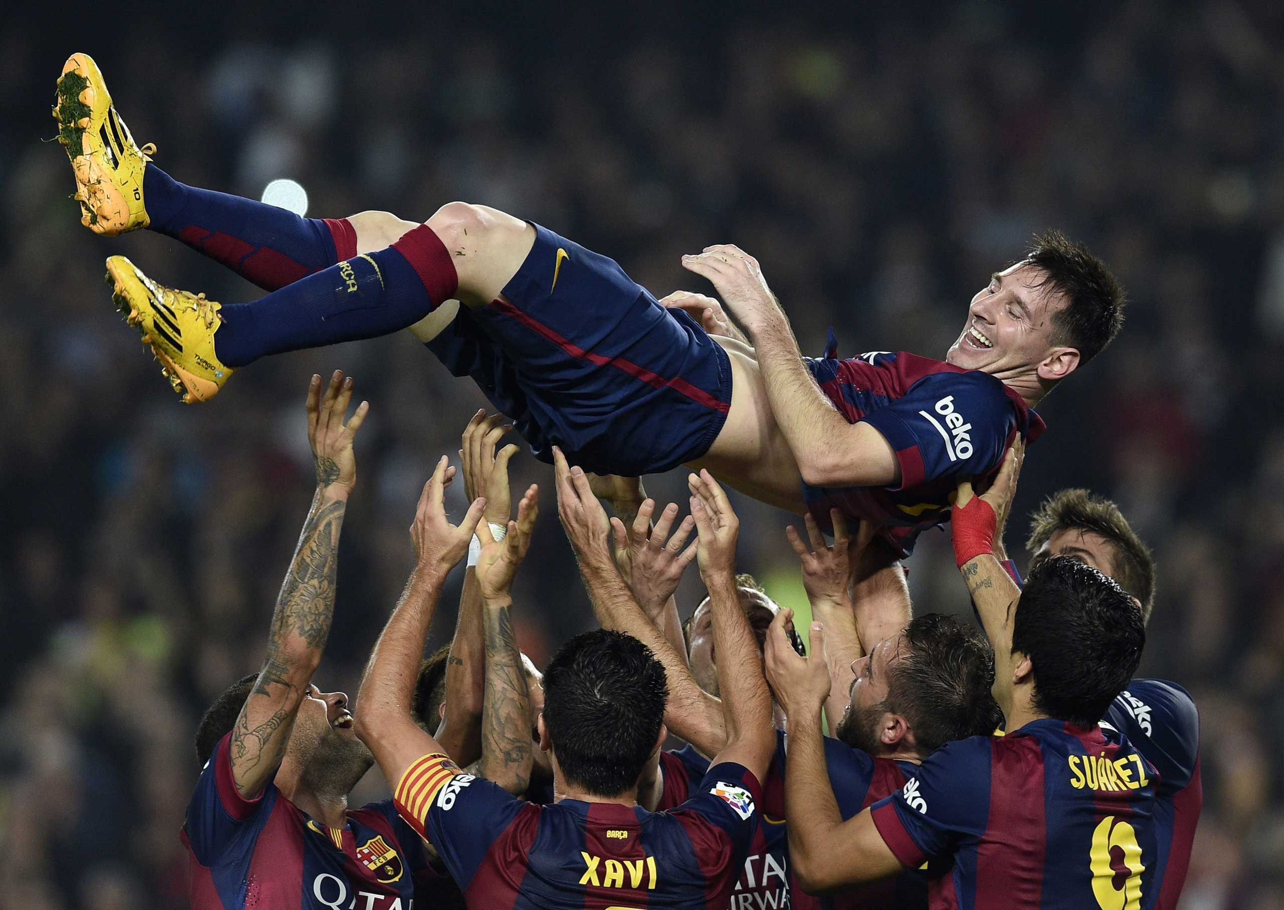Nov. 22, 2014. Barcelona's Argentinian forward Lionel Messi is thrown into the air by his teammates as they celebrate his new record after he scored during the Spanish league football match FC Barcelona versus Sevilla FC at the Camp Nou stadium in Barcelona. Lionel Messi broke Telmo Zarra's 59-year-old record as the leading goalscorer in the history of La Liga.