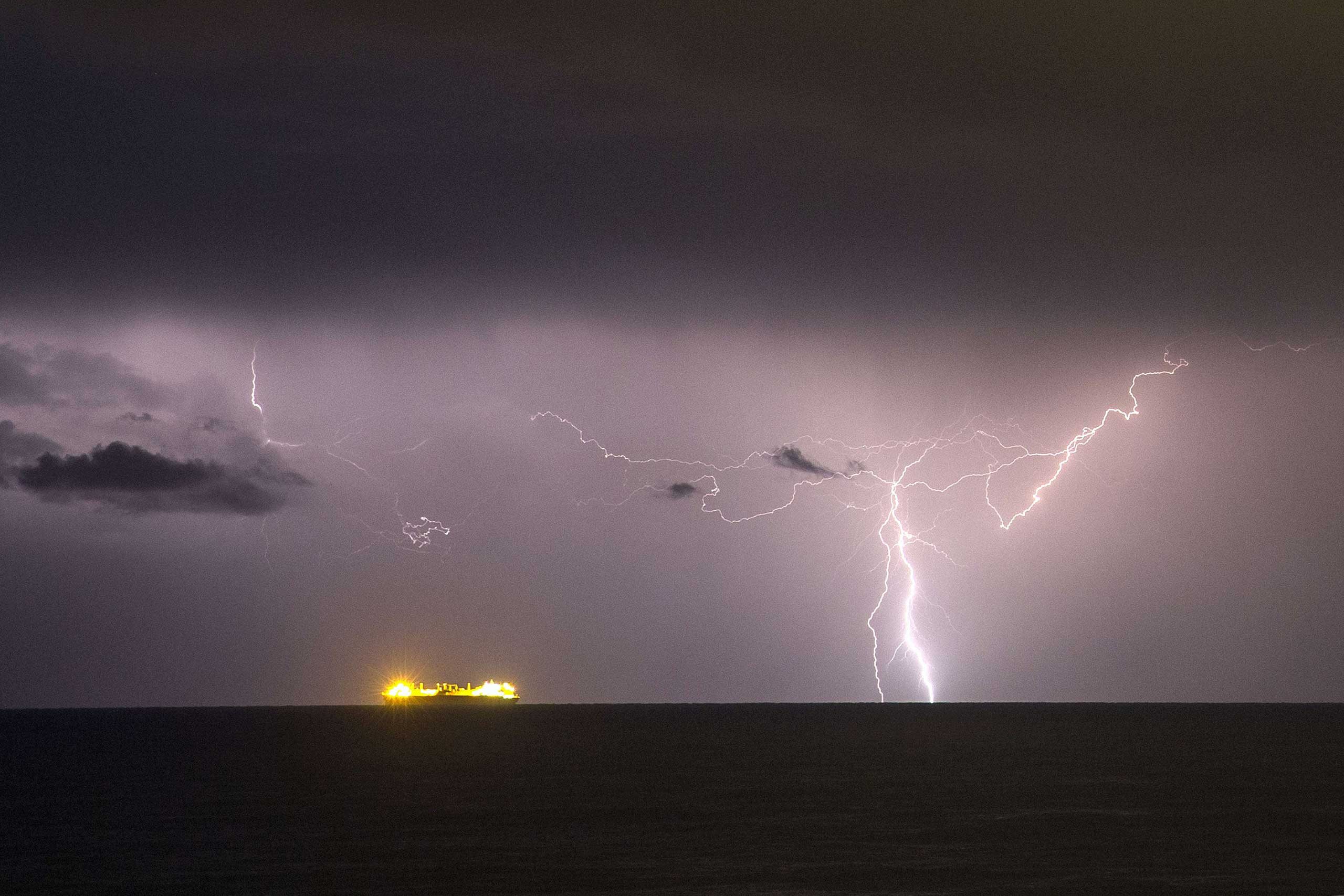 Nov. 24, 2014. A ship sails in the Mediterranean Sea as lightning strikes the sky as seen from the Israeli coastal moshav of Mikhmoret, north of Tel Aviv.