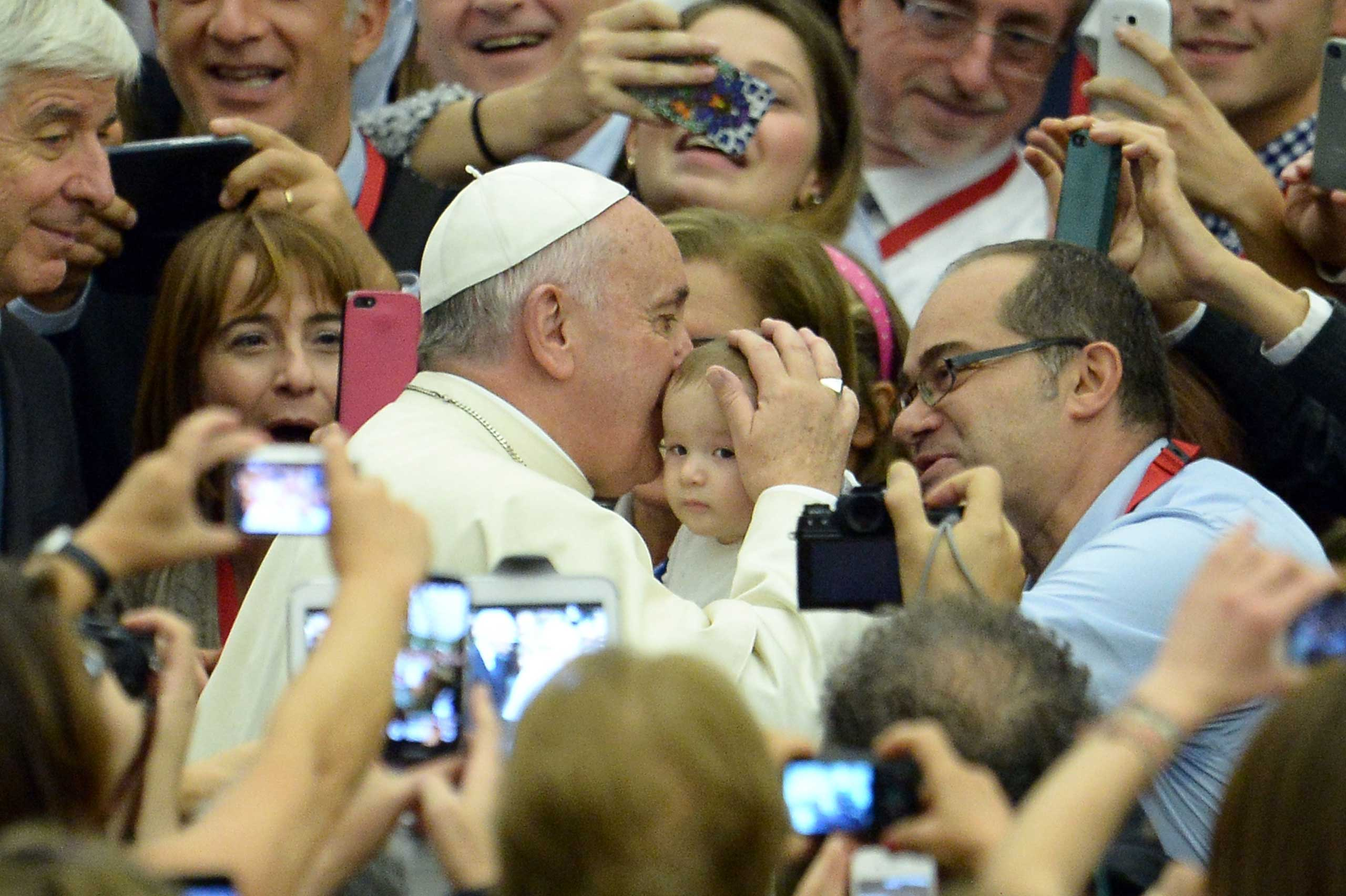 Pope Francis kisses a baby during an audience with members of the Association of Italian Catholic Doctors at Paul VI audience hall at the Vatican on Nov. 15, 2014.