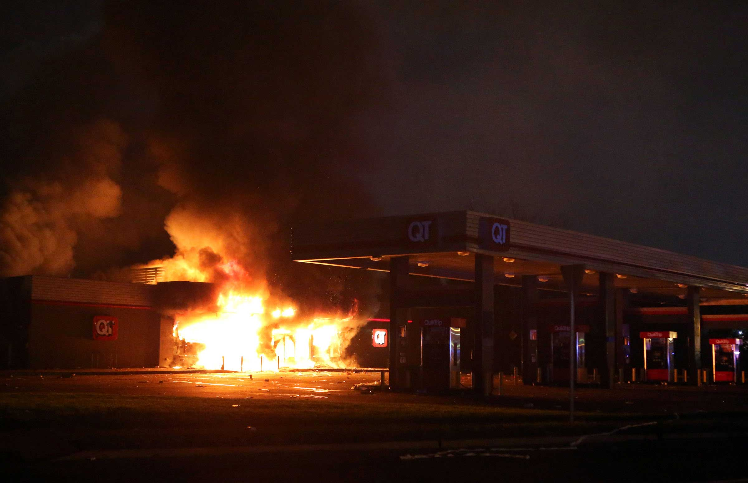A fire burns at a QuikTrip store in Ferguson on Aug. 10, 2014, as protests turned violent one day after Brown's death. The night marked the first violent turn for the protests.