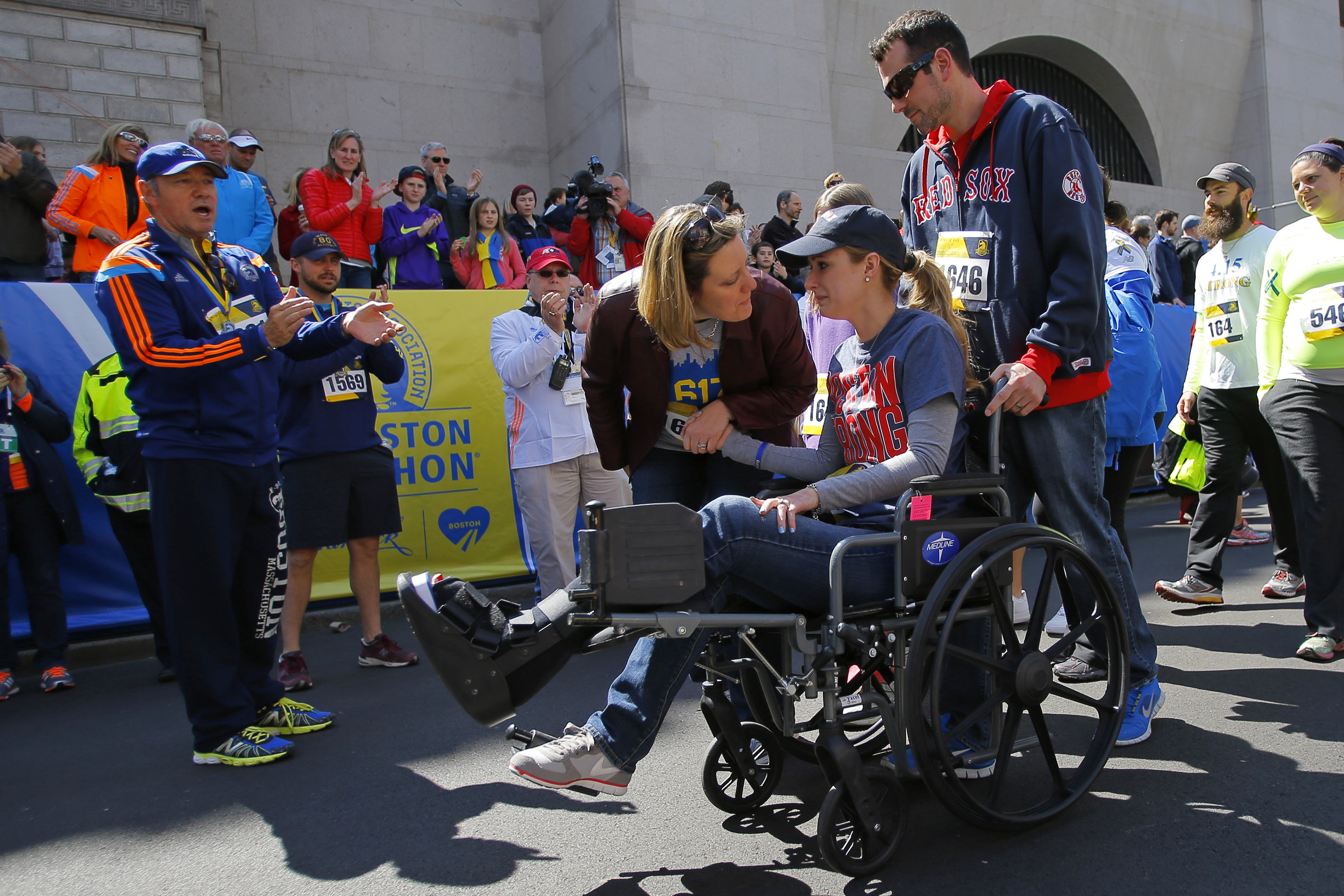 Actor Kevin Spacey (L) cheers on as 2013 Boston Marathon bombing survivor Rebekah Gregory DiMartino (2nd R) crosses the marathon finish line during a Tribute Run for survivors and first responders in Boston on April 19, 2014.