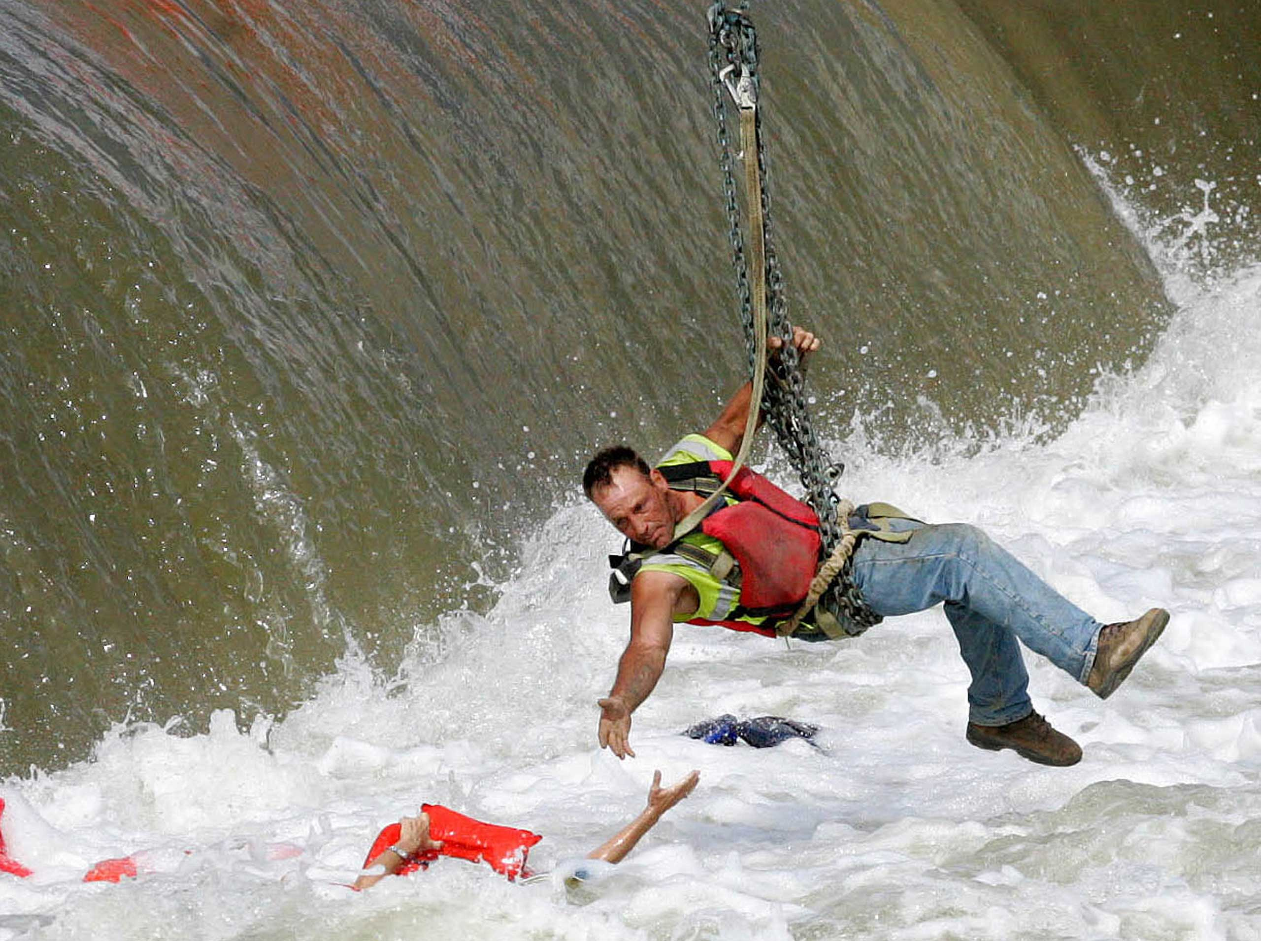 A local construction worker, suspended from a crane, rescues a woman who fell into the Des Moines River in Des Moines, Iowa in 2009.