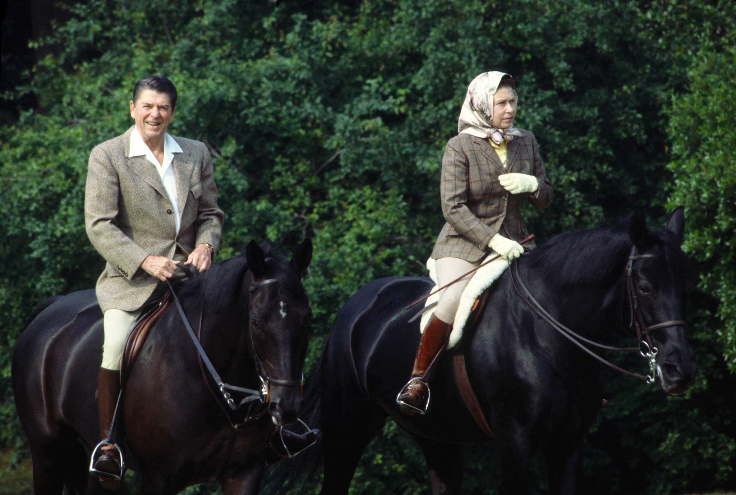 During a State Visit, Queen Elizabeth II rides her horse in Windsor Great Park with President Ronald Reagan in the United Kingdom in 1982.