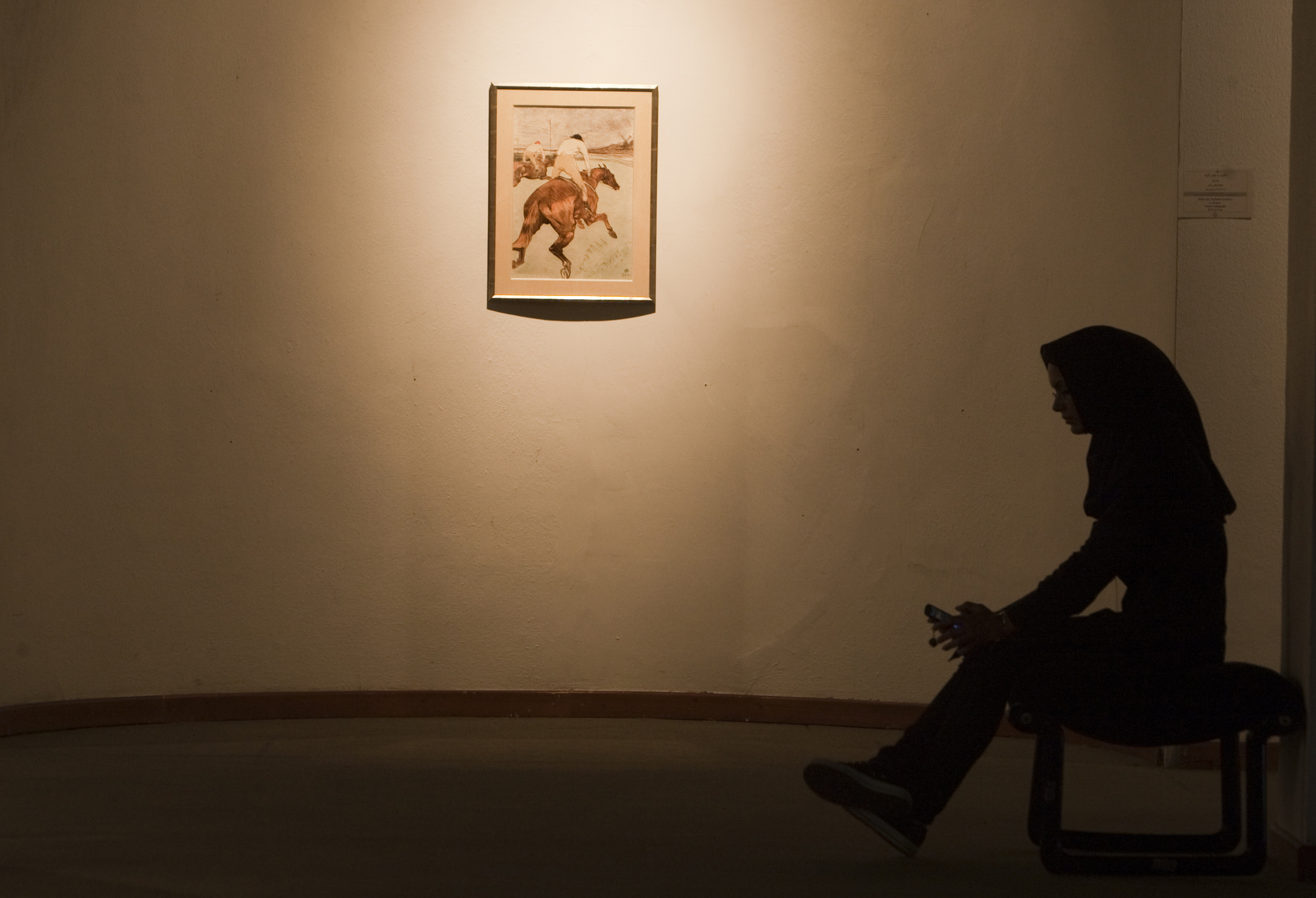 A security personnel sits next to a painting by the 20th century French painter Henri de Toulouse-Lautrec at Tehran's Museum of Contemporary Art on June 19, 2010