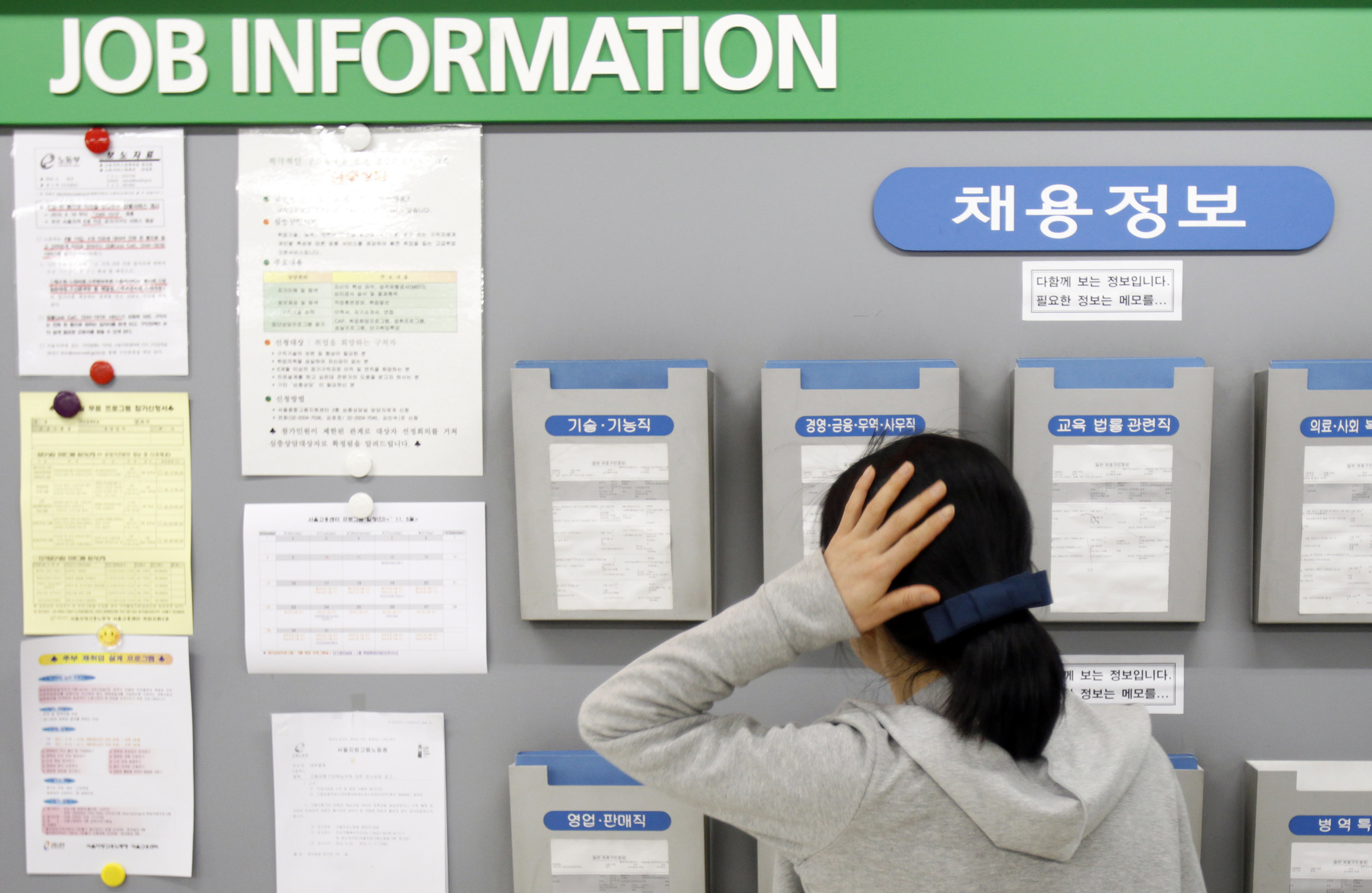 A job seeker looks at a board showing job information at an office of the Employment Information Service in Seoul on May 11, 2011
