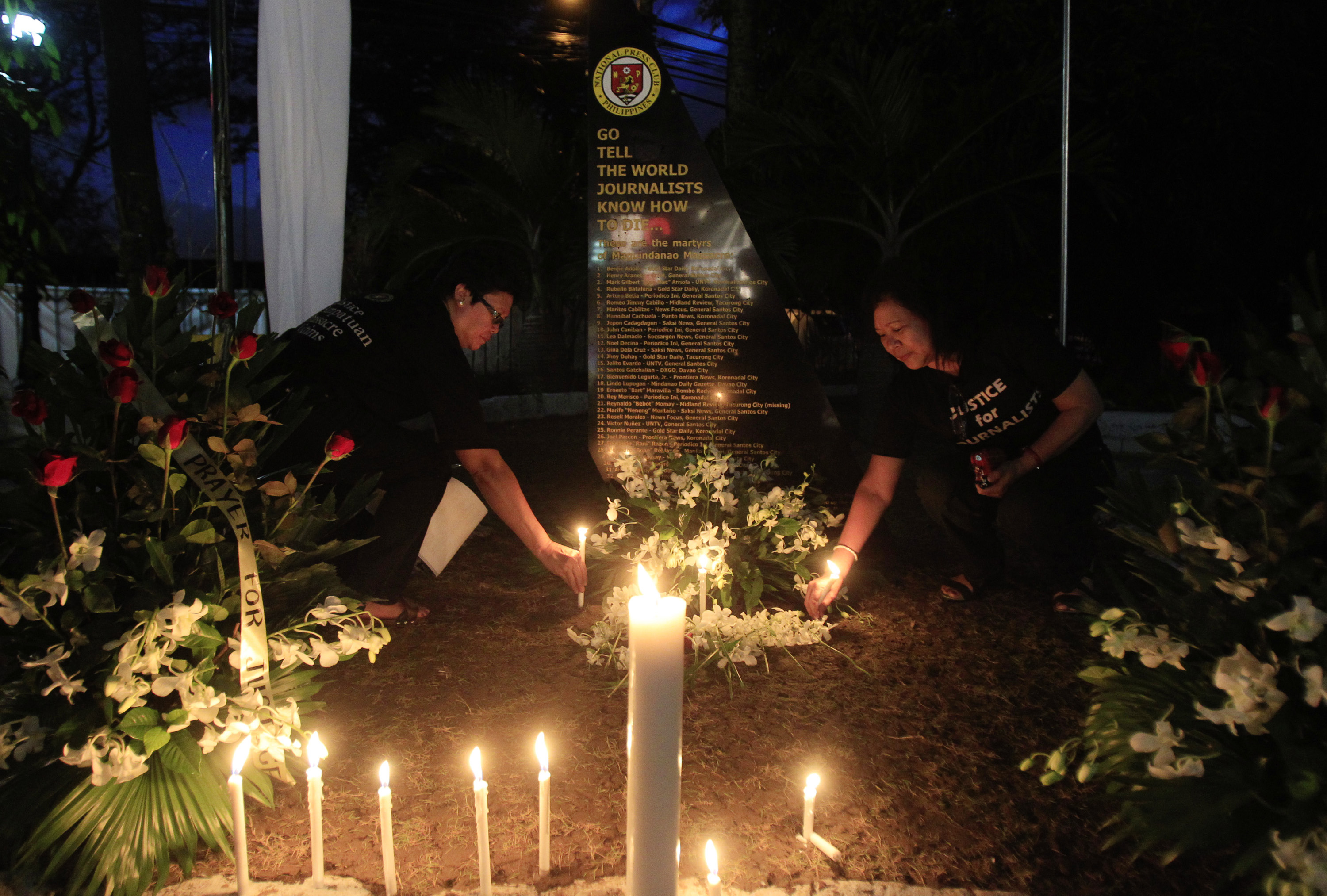 Filipino journalists light candles to commemorate the second-year anniversary of the Maguindanao massacre at the National Press Club compound in Manila on Nov. 23, 2011