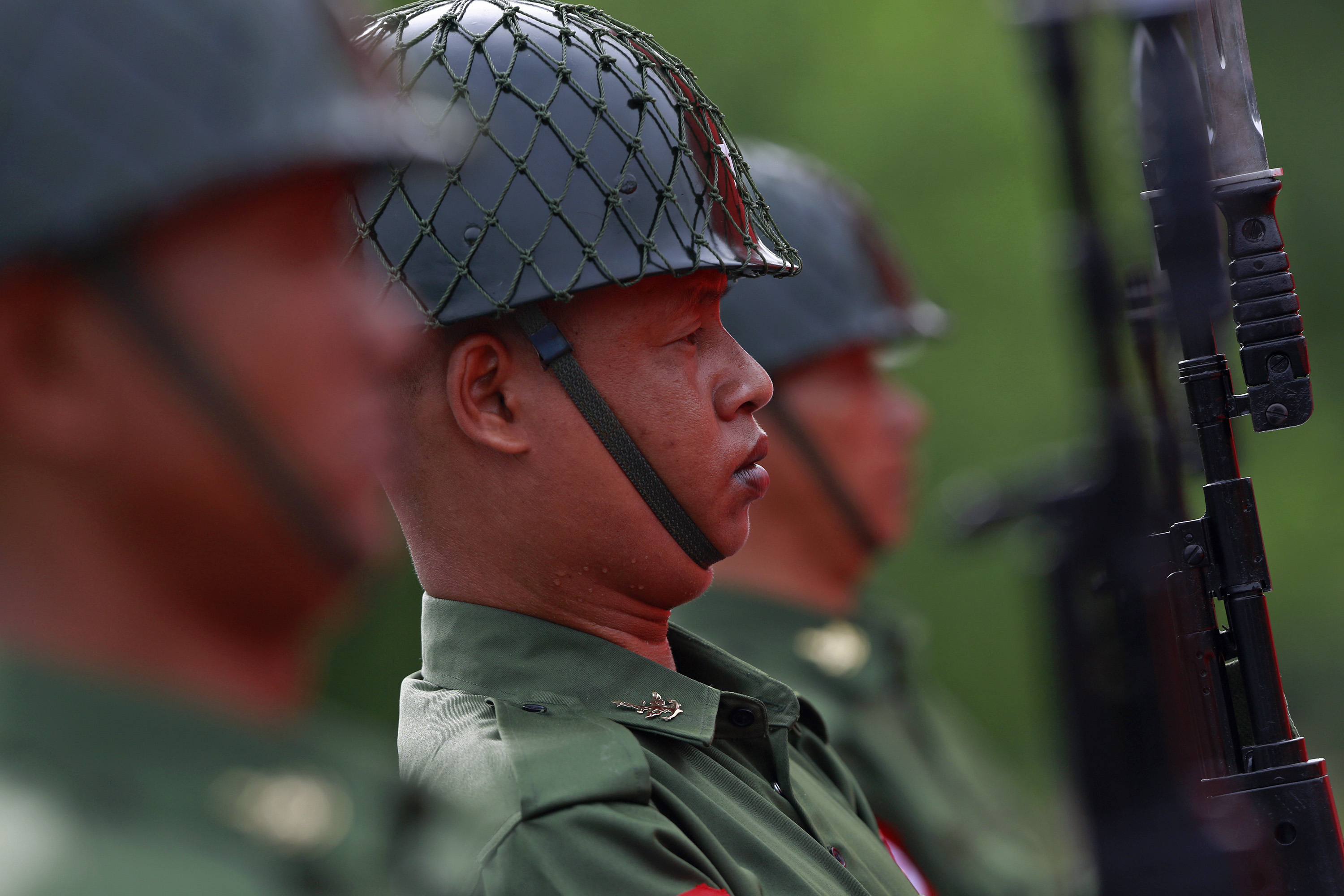 Burmese soldiers salute during an event marking the anniversary of Martyrs' Day at the Martyrs' Mausoleum in Rangoon on July 19, 2014