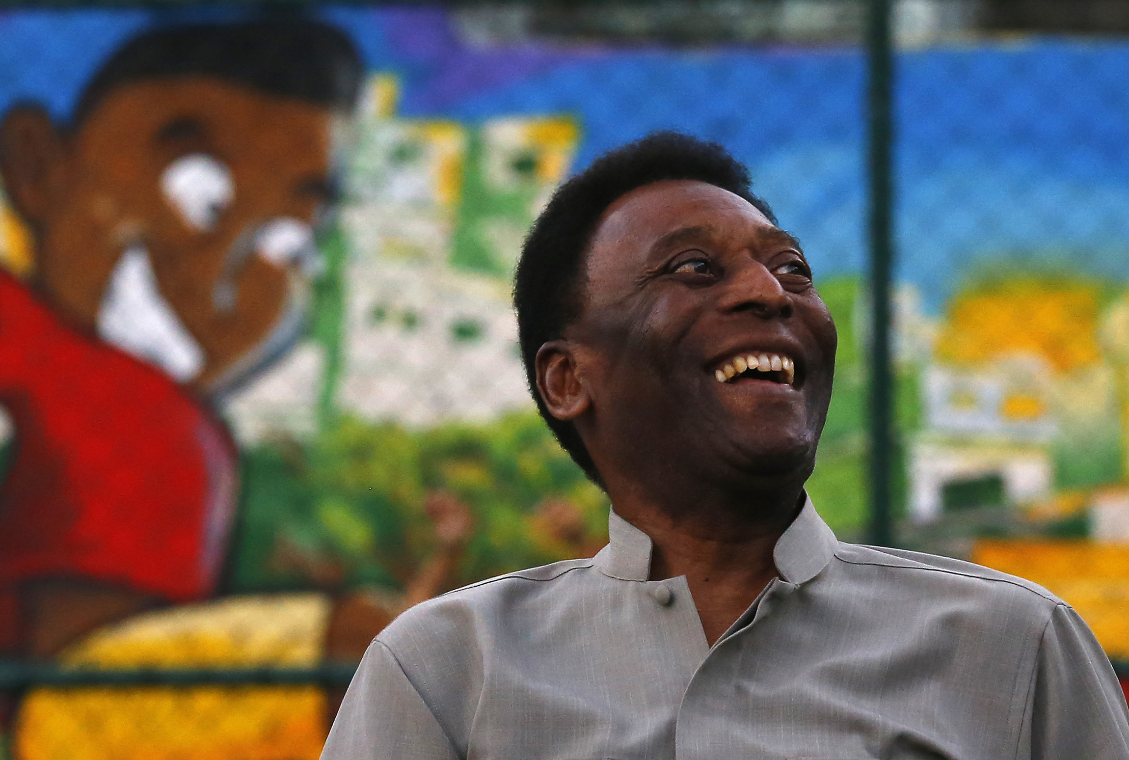 Brazilian soccer legend Pelé laughs during the inauguration of a refurbished soccer field at the Mineira slum in Rio de Janeiro on Sept. 10, 2014