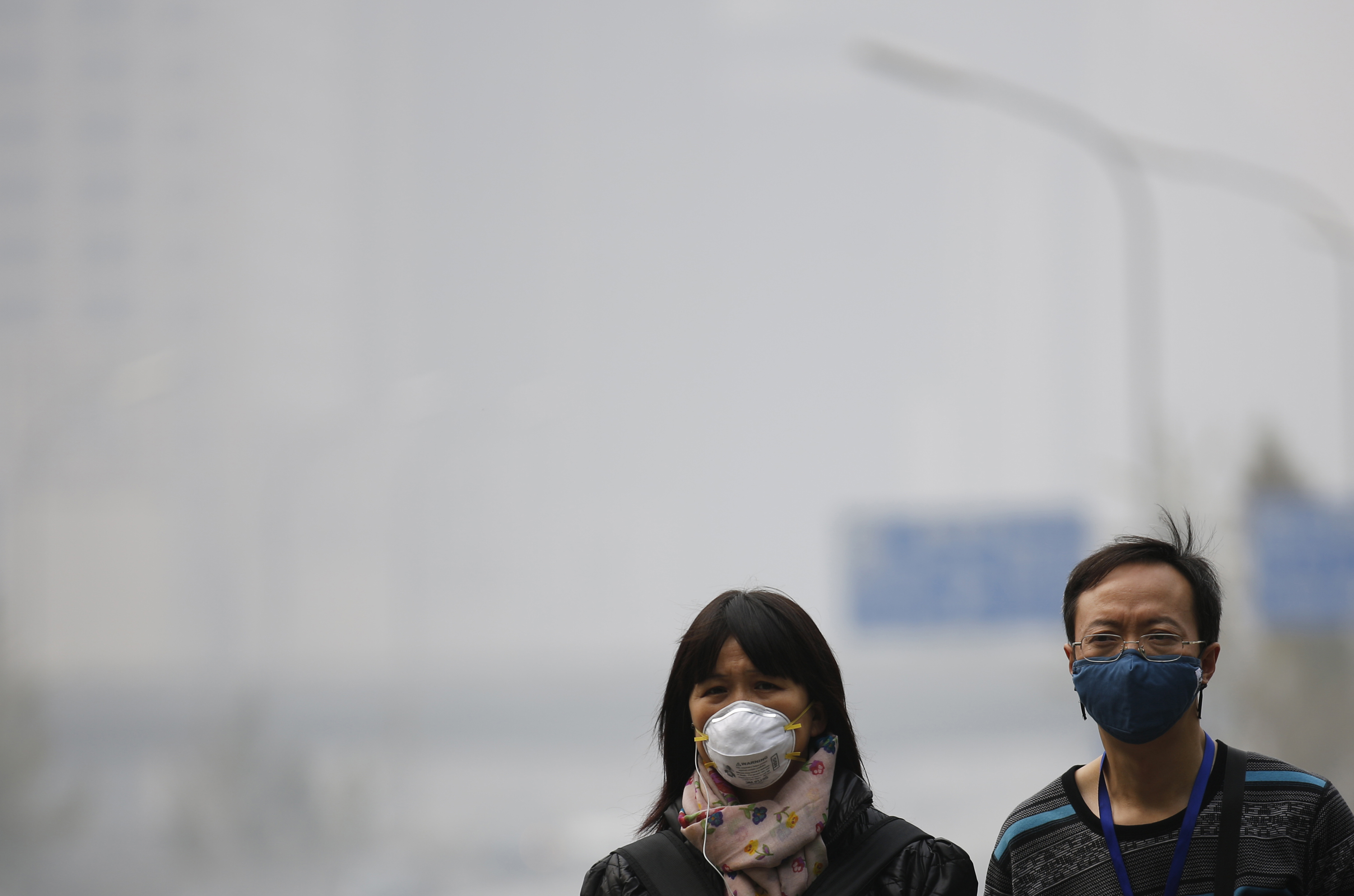 People wearing masks walk on a street amid heavy haze and smog in Beijing on Oct. 11, 2014
