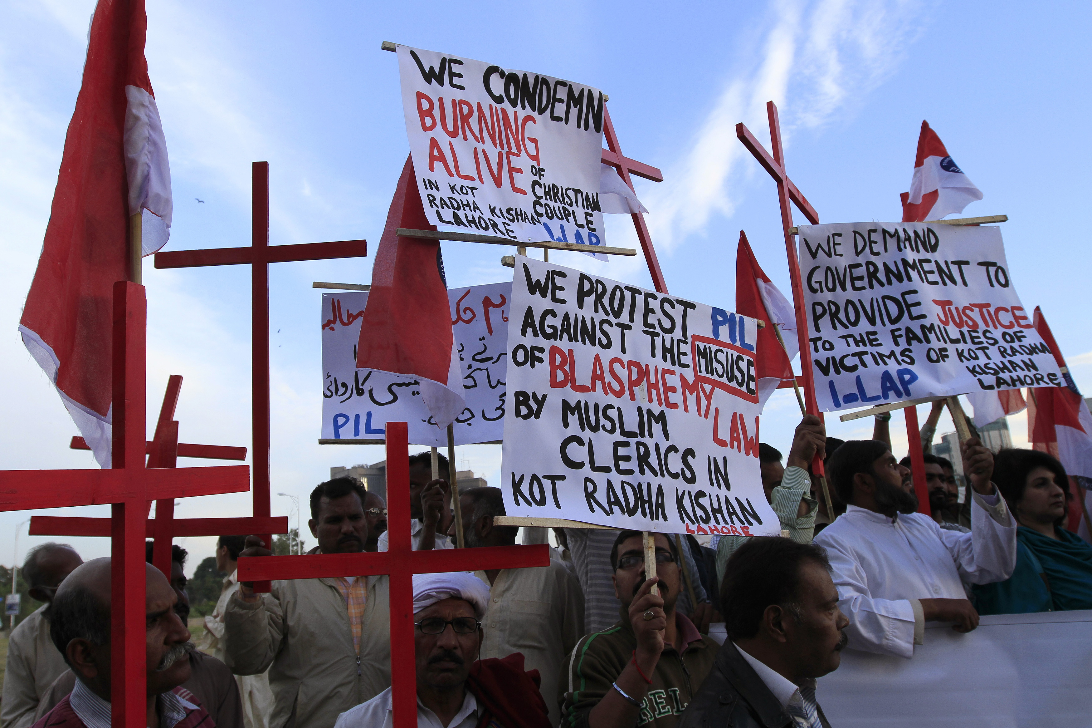 Members of the Pakistani Christian community hold placards and crosses in Islamabad Nov. 5, 2014, during a demonstration to condemn the death of a Christian couple in a village in Punjab province
