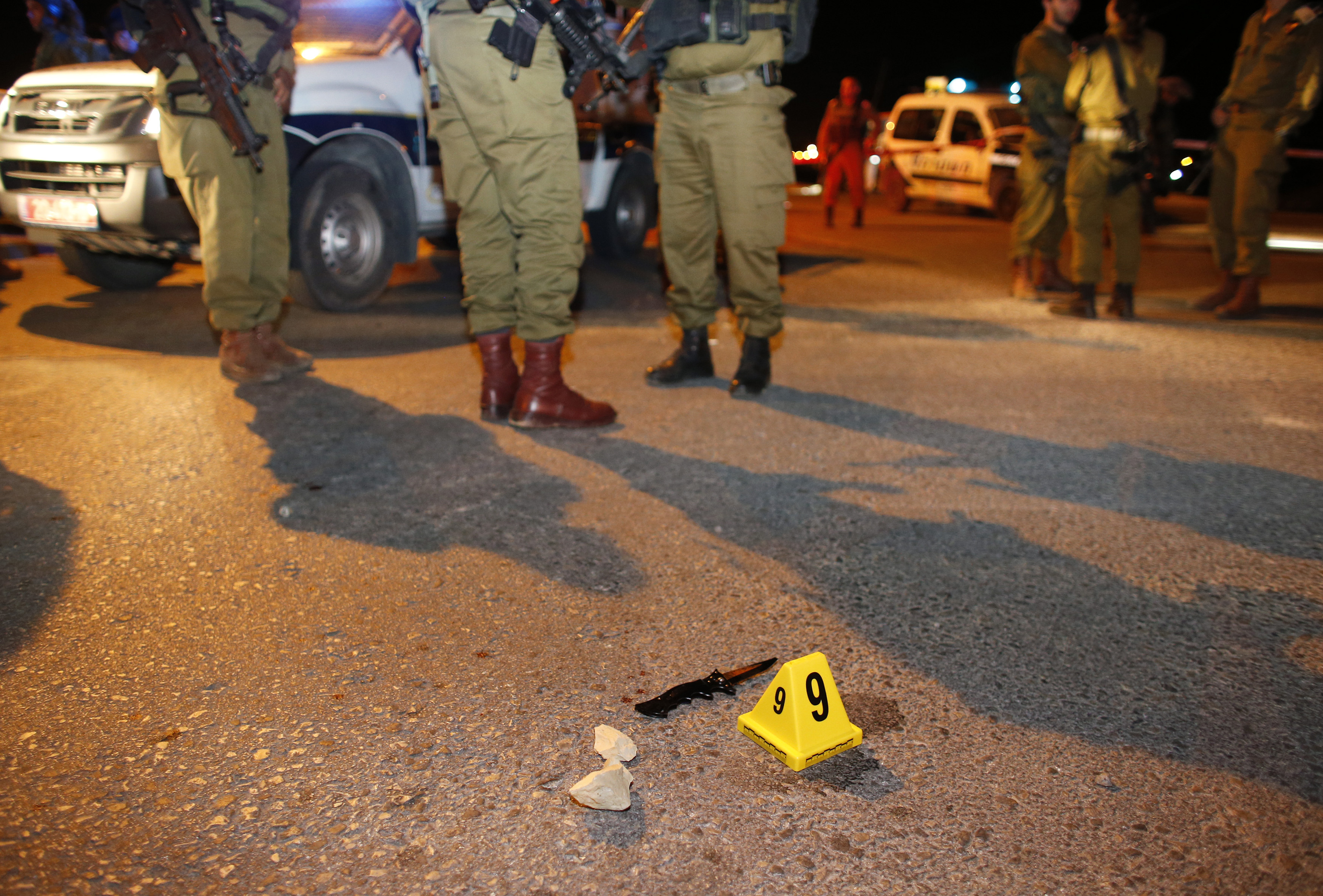 Israeli soldiers stand near a knife at the scene of a stabbing attack near the Jewish settlement of Alon Shvut in the West Bank on Nov. 10, 2014