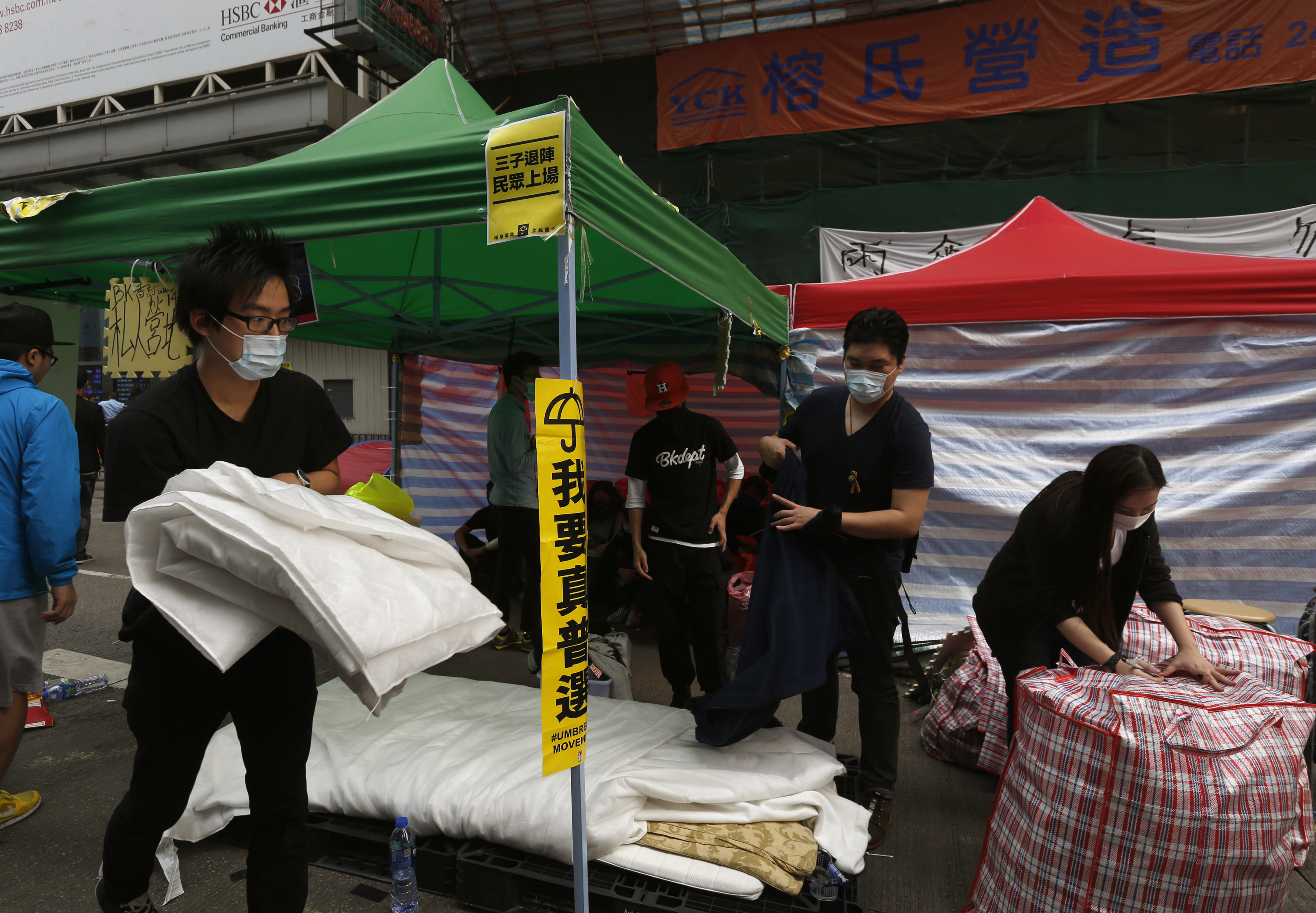 Masked pro-democracy protesters who have occupied a street at Mong Kok shopping district in Hong Kong  pack their belongings on Nov. 19, 2014, before they are removed by bailiffs under a court injunction