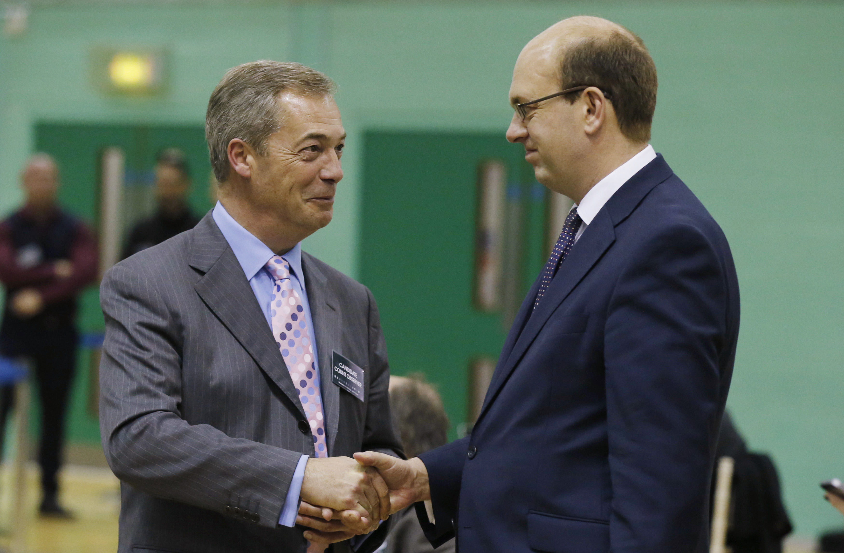 Nigel Farage, left, leader of the U.K. Independence Party, shakes hands with Mark Reckless, the former Conservative Party MP for Rochester and Strood, during the by-election ballot count at Medway Park in Gillingham, England, on Nov. 21, 2014