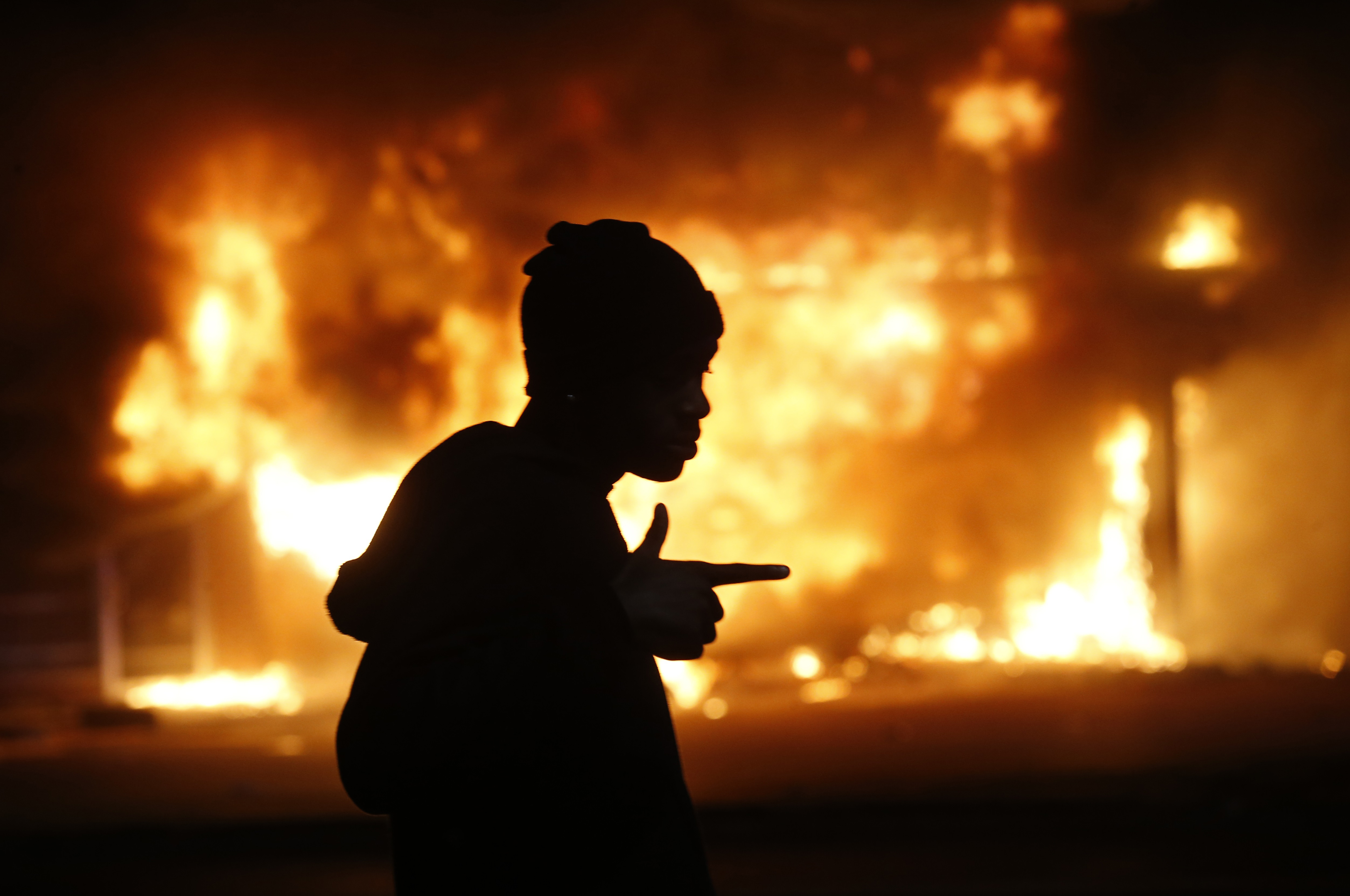 A man walks past a burning building during rioting after a grand jury returned no indictment in the shooting of Michael Brown in Ferguson, Missouri November 24, 2014.