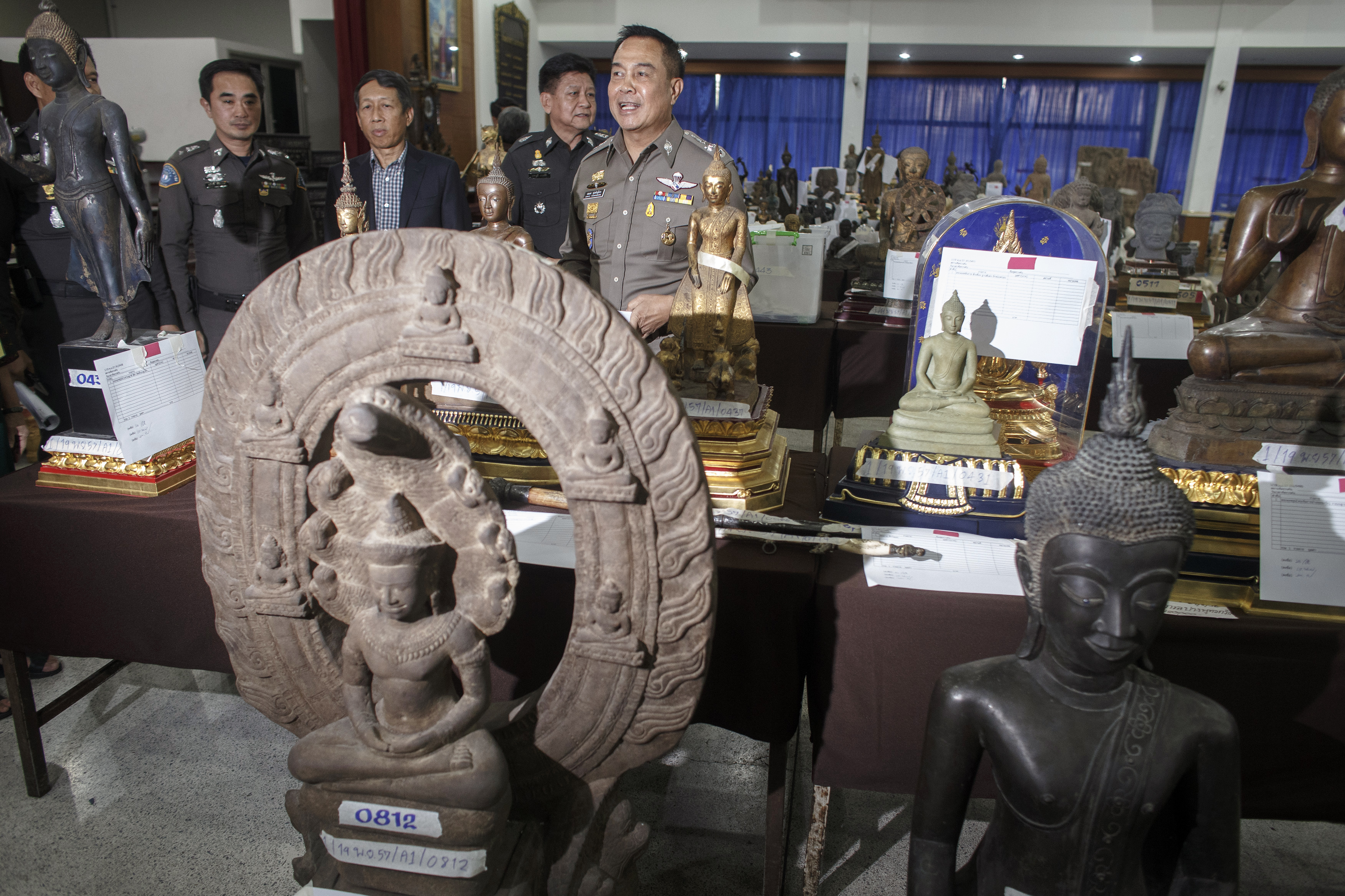 General Somyot Poompanmuang, chief of Royal Thai Police, stands among antique Buddha statues that were seized during an investigation into former Central Investigation Bureau chief Pongpat Chayaphan, at a military base in Bangkok on Nov. 26, 2014