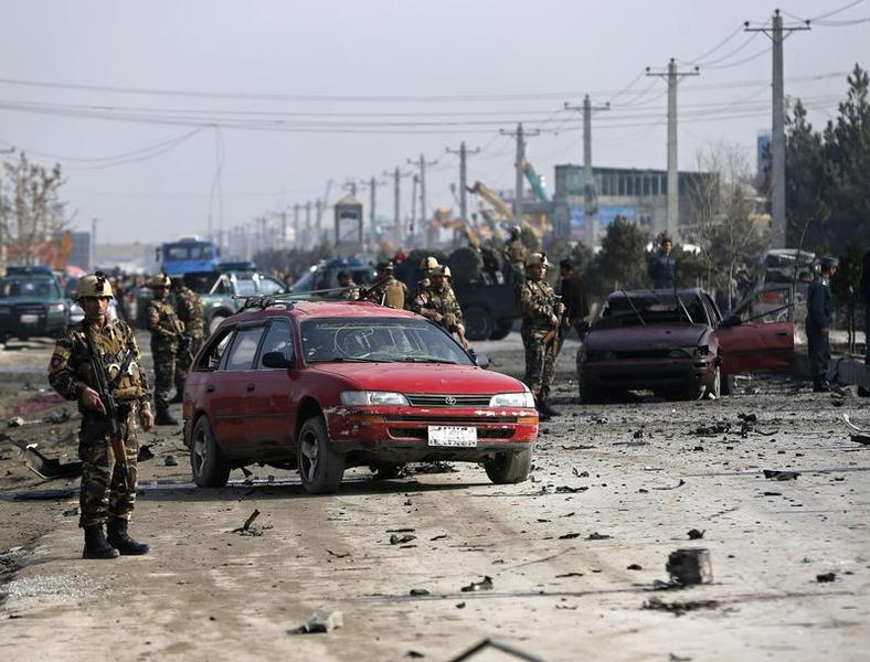 Afghan security forces inspect the site of a suicide attack on a British embassy vehicle in Kabul on Nov. 27, 2014