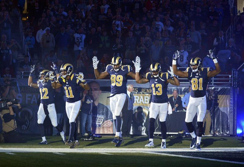 St. Louis Rams players put their hands up to show support for Michael Brown before a game against the Oakland Raiders at the Edward Jones Dome, St. Louis, on Nov. 30, 2014