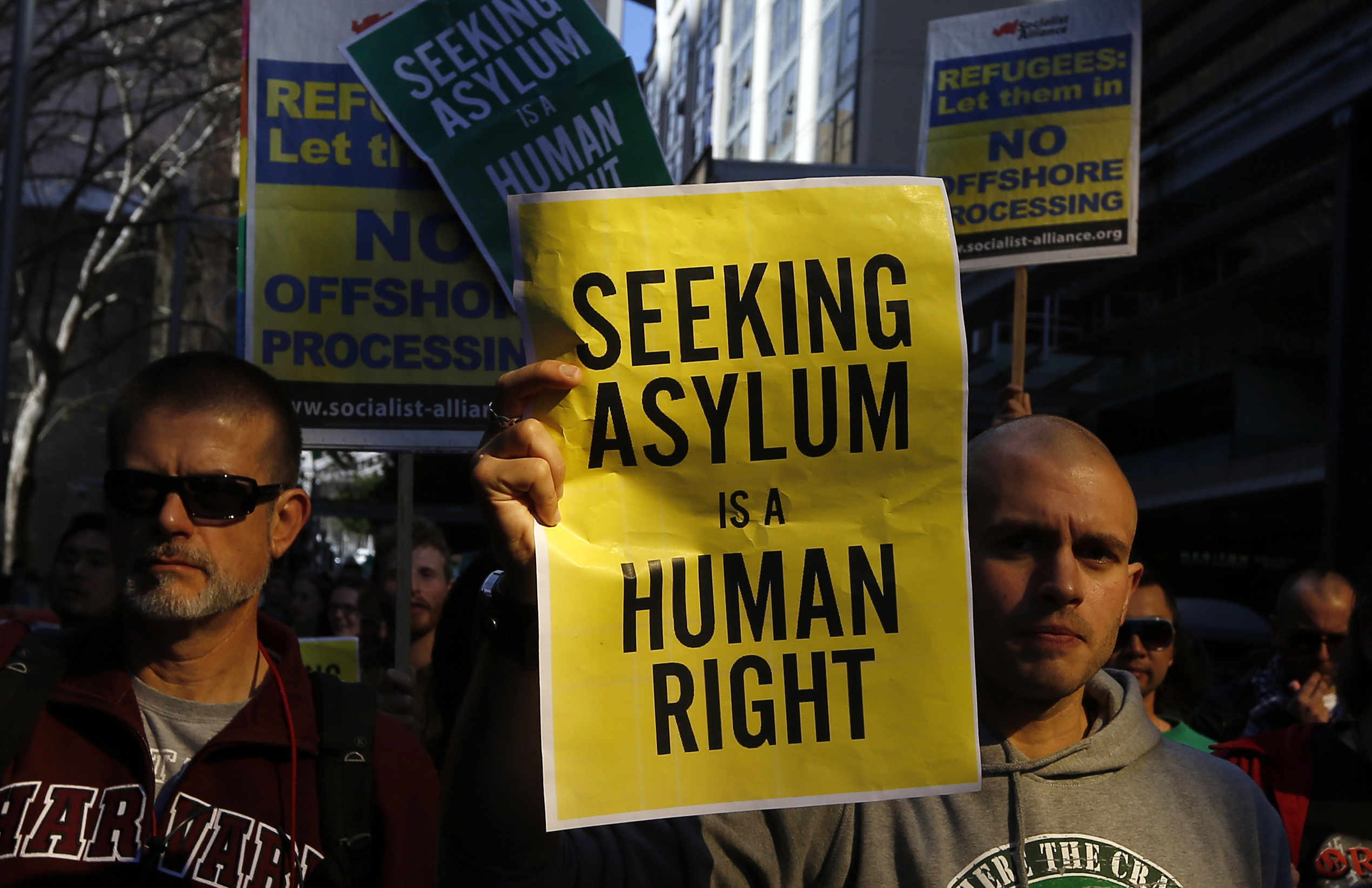 A man holds a poster during a rally in support of asylum seekers in central Sydney July 20, 2013