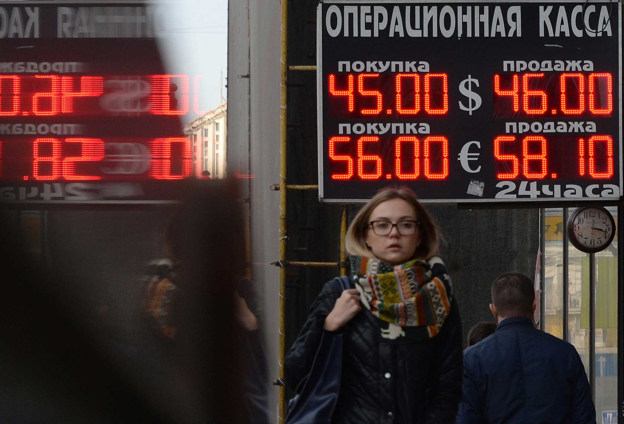 Pedestrians walk under a board listing foreign currency rates against the Russian ruble outside an exchange office in central Moscow on November 10, 2014.