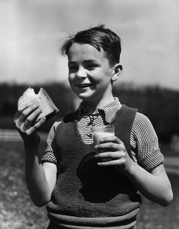 A boy eating a sandwich, circa 1945
