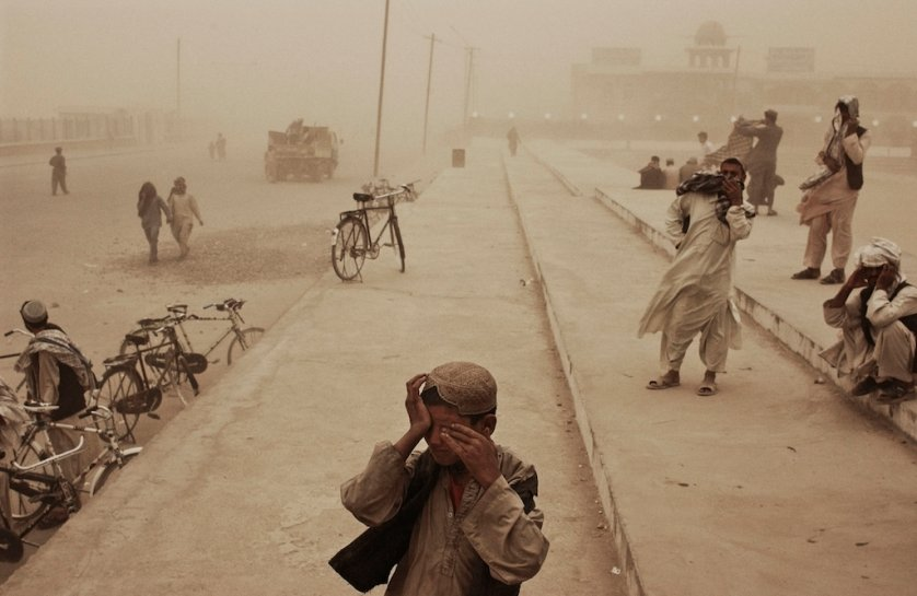 Afghanistan. Kandahar. March 2005. A boy covers his eyes during a sandstorm in the southern city of Kandahar.