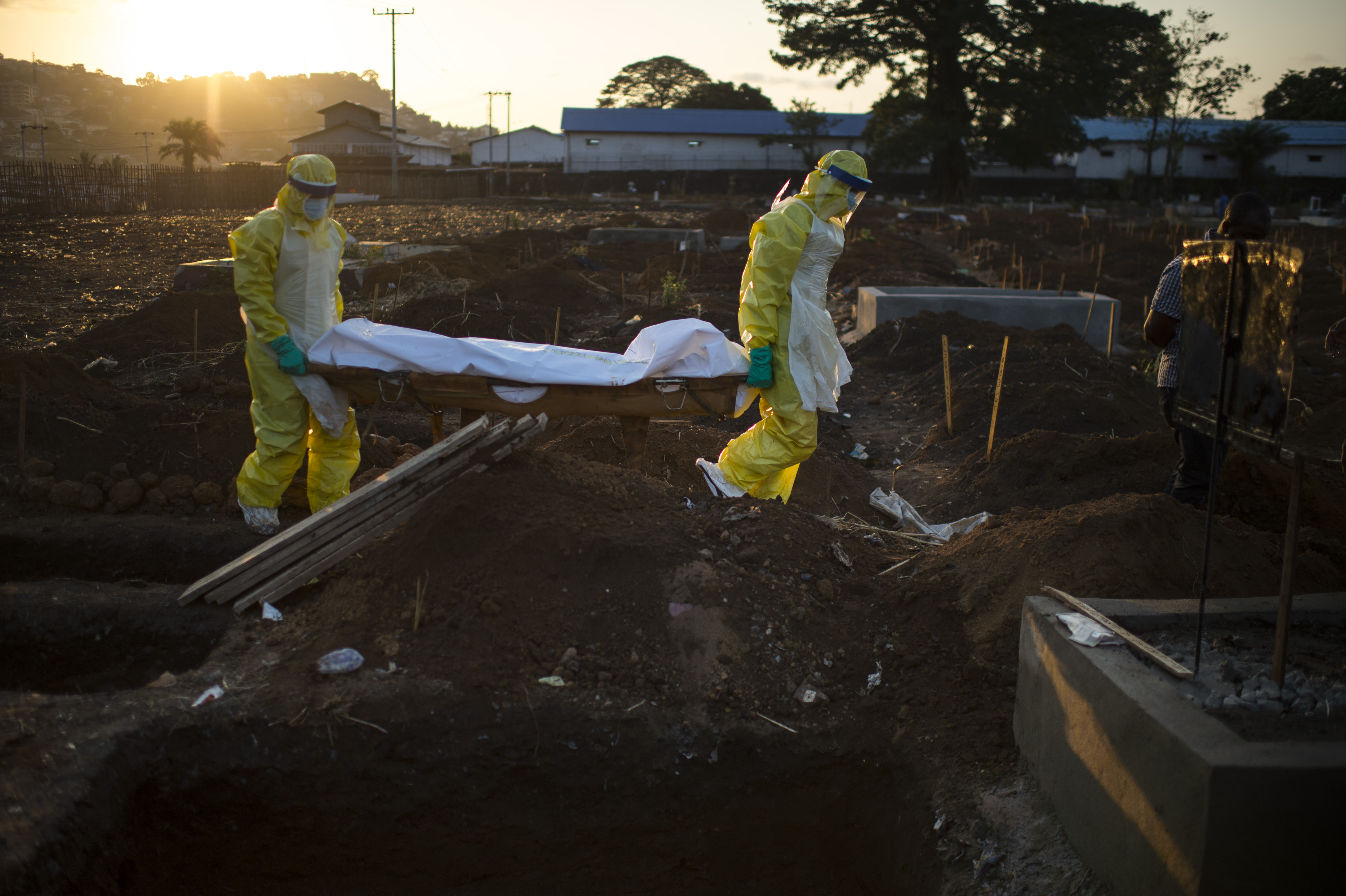 Members of the burial team carry a body to his grave at King Tom Cemetery in Freetown, Sierra Leone, on Nov. 19, 2014.