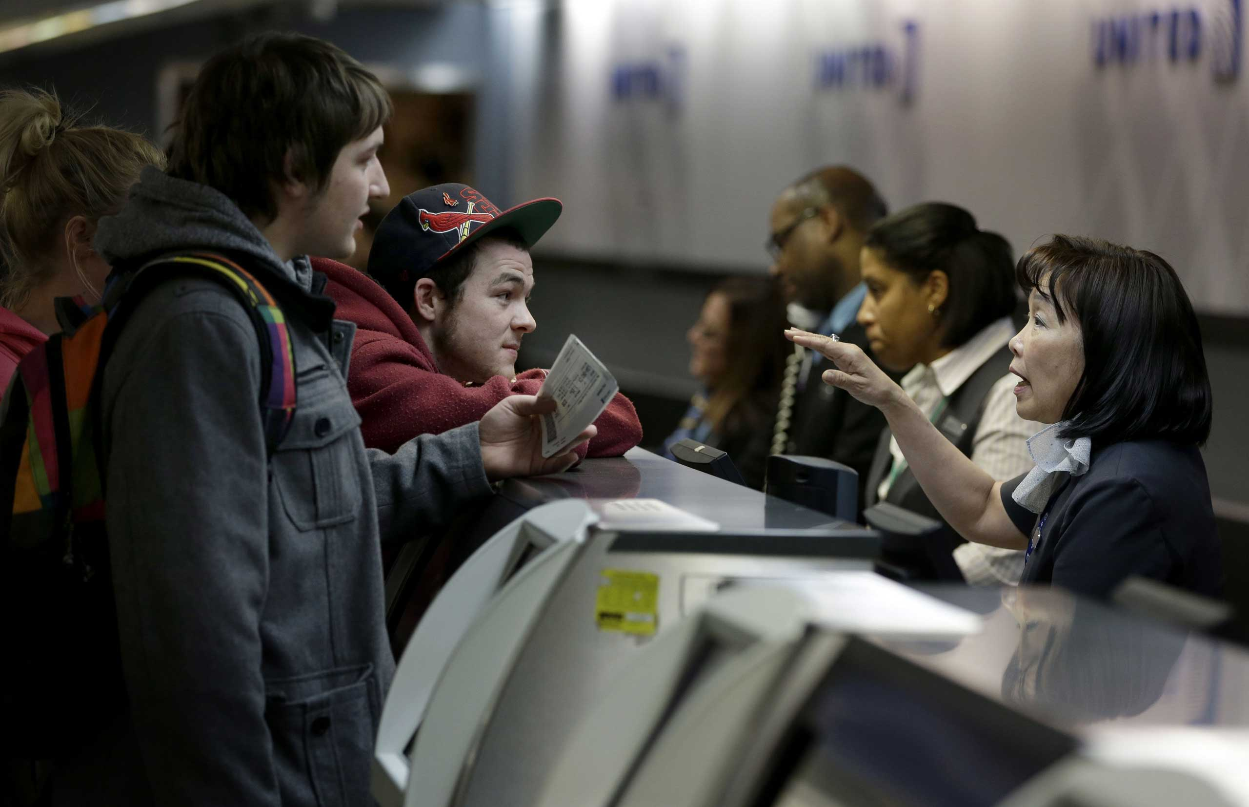 Brandon Bybee, left, and Cory McKenrick, second from left, talk with a ticket agent to try and move up their flight to Illinois in order to beat an expected snow storm at LaGuardia Airport in New York City on Jan. 26, 2015.